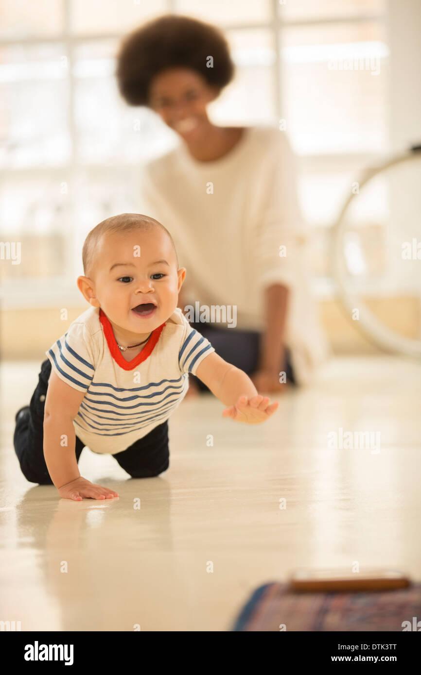 Mother watching baby boy crawl on floor - Stock Image