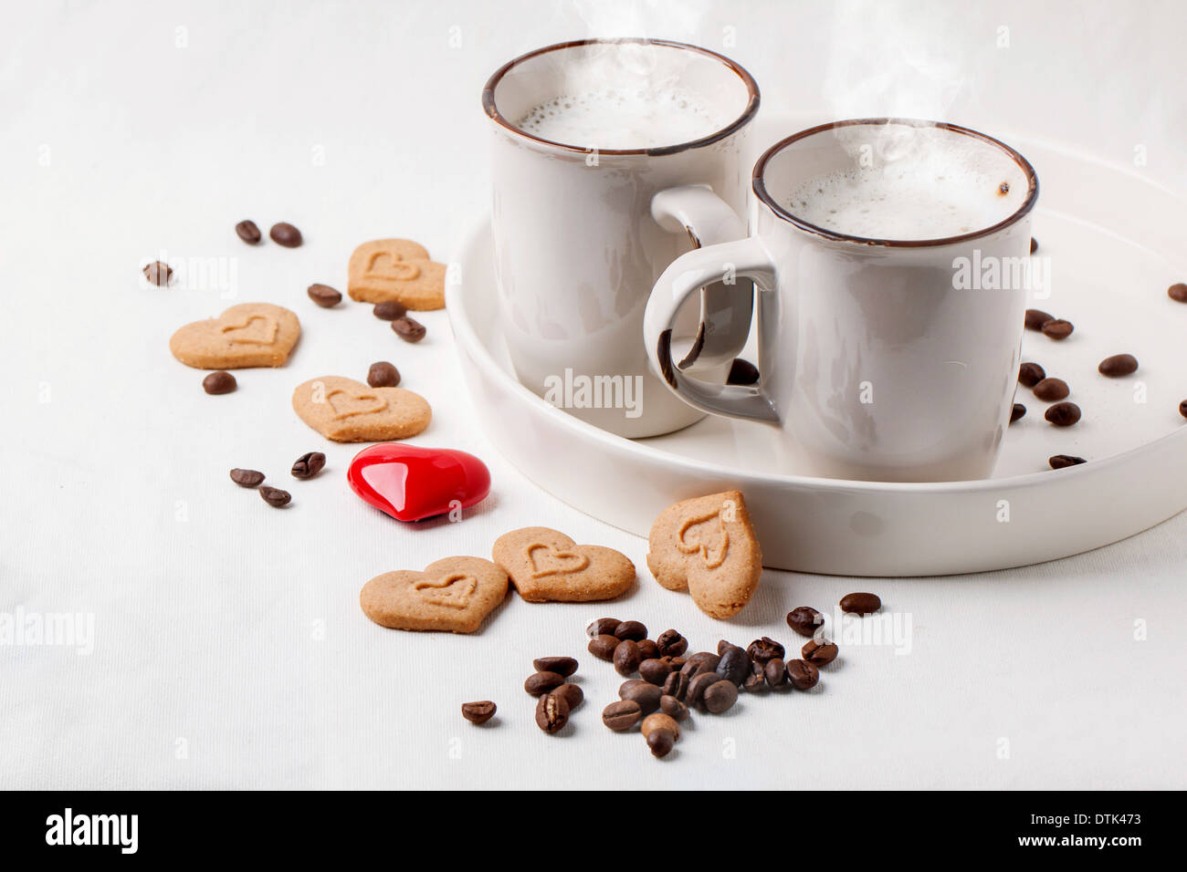 Two cups of cappuccino served with spices and cookies as hearts and one red heart on white textile. - Stock Image