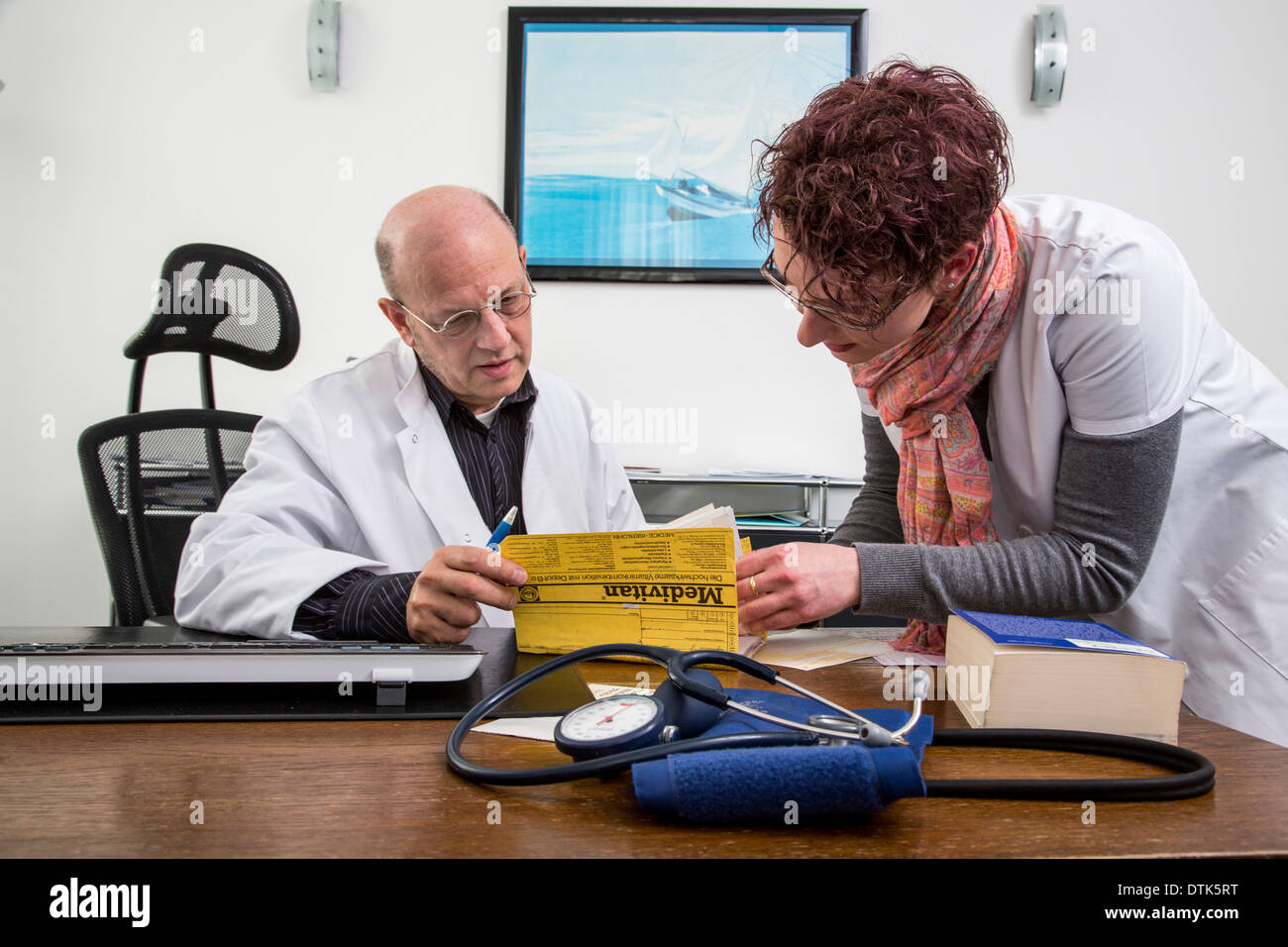 Doctors office. Doctor confers with an assistant. - Stock Image