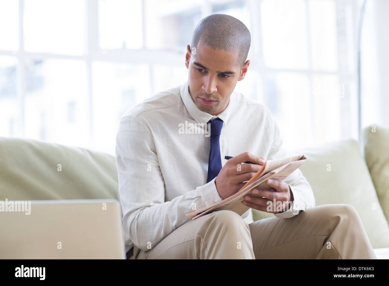 Businessman making notes from laptop on sofa - Stock Image