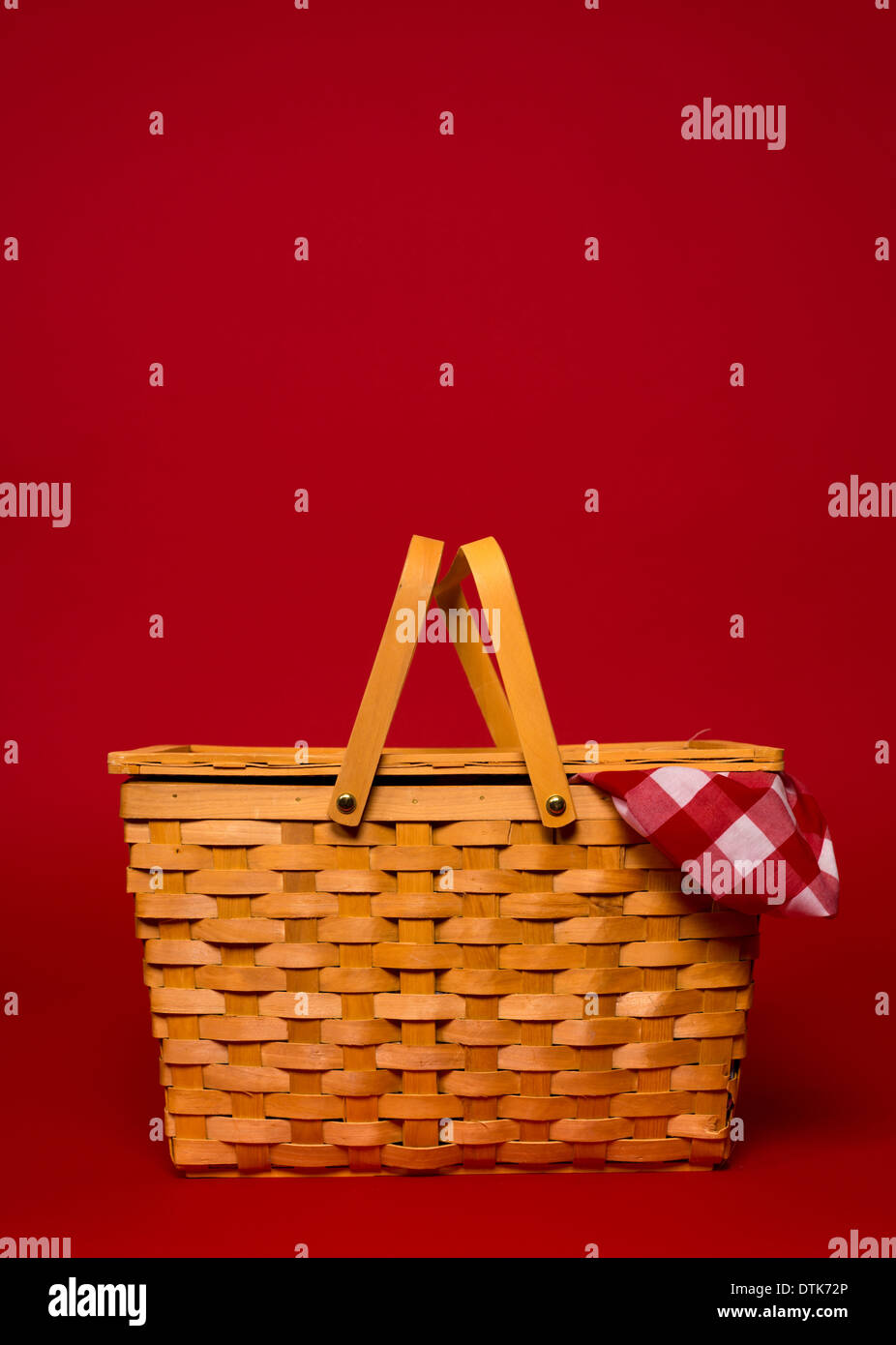 A brown, wicker picnic basket with red gingham tablecloth on a red background with copy space - Stock Image