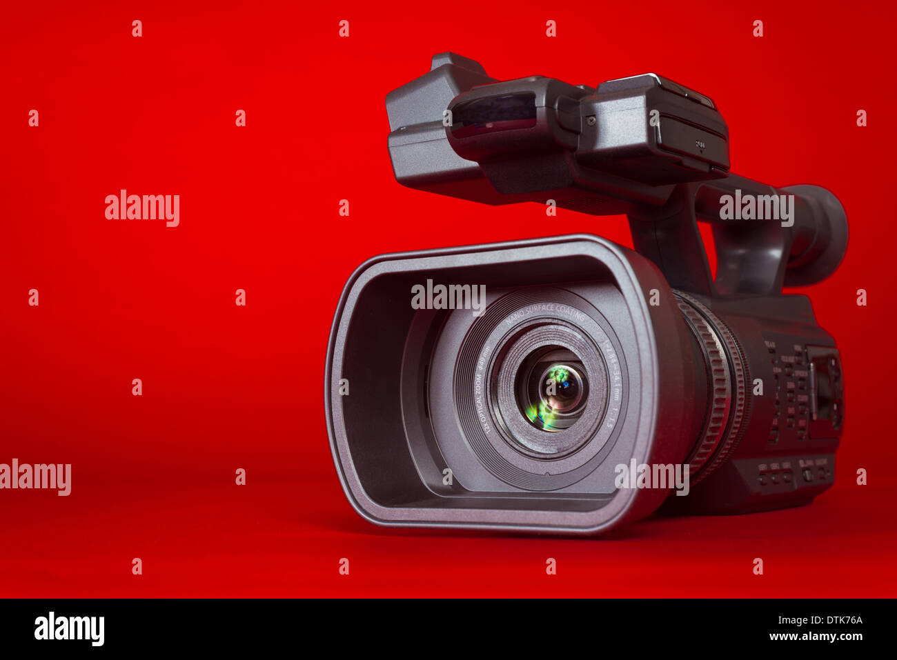 A black video camera on a red background with copy space - Stock Image