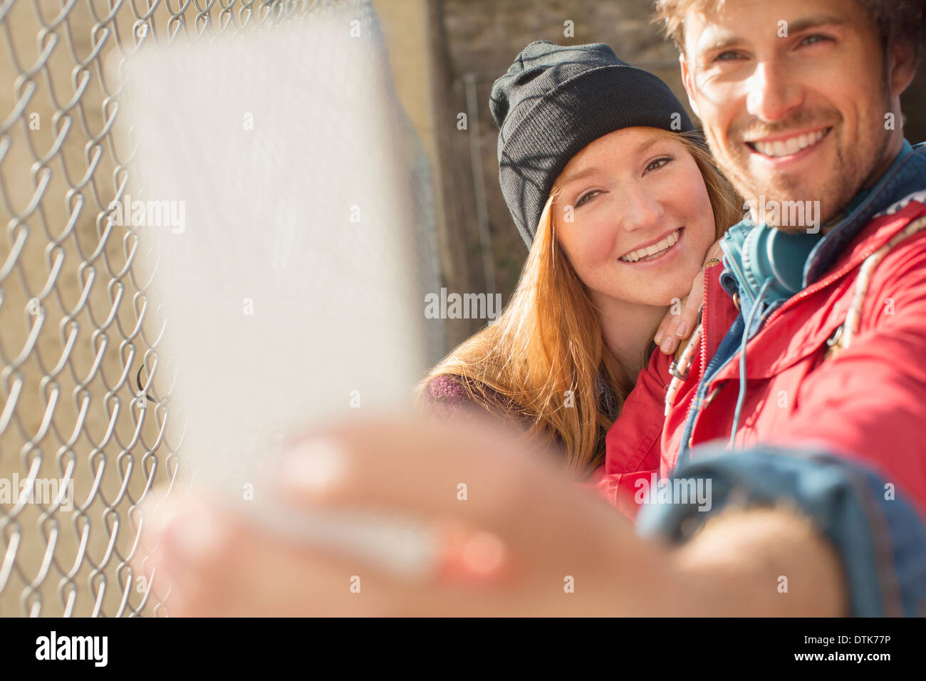 Couple taking self-portrait with camera phone next to chain link fence - Stock Image