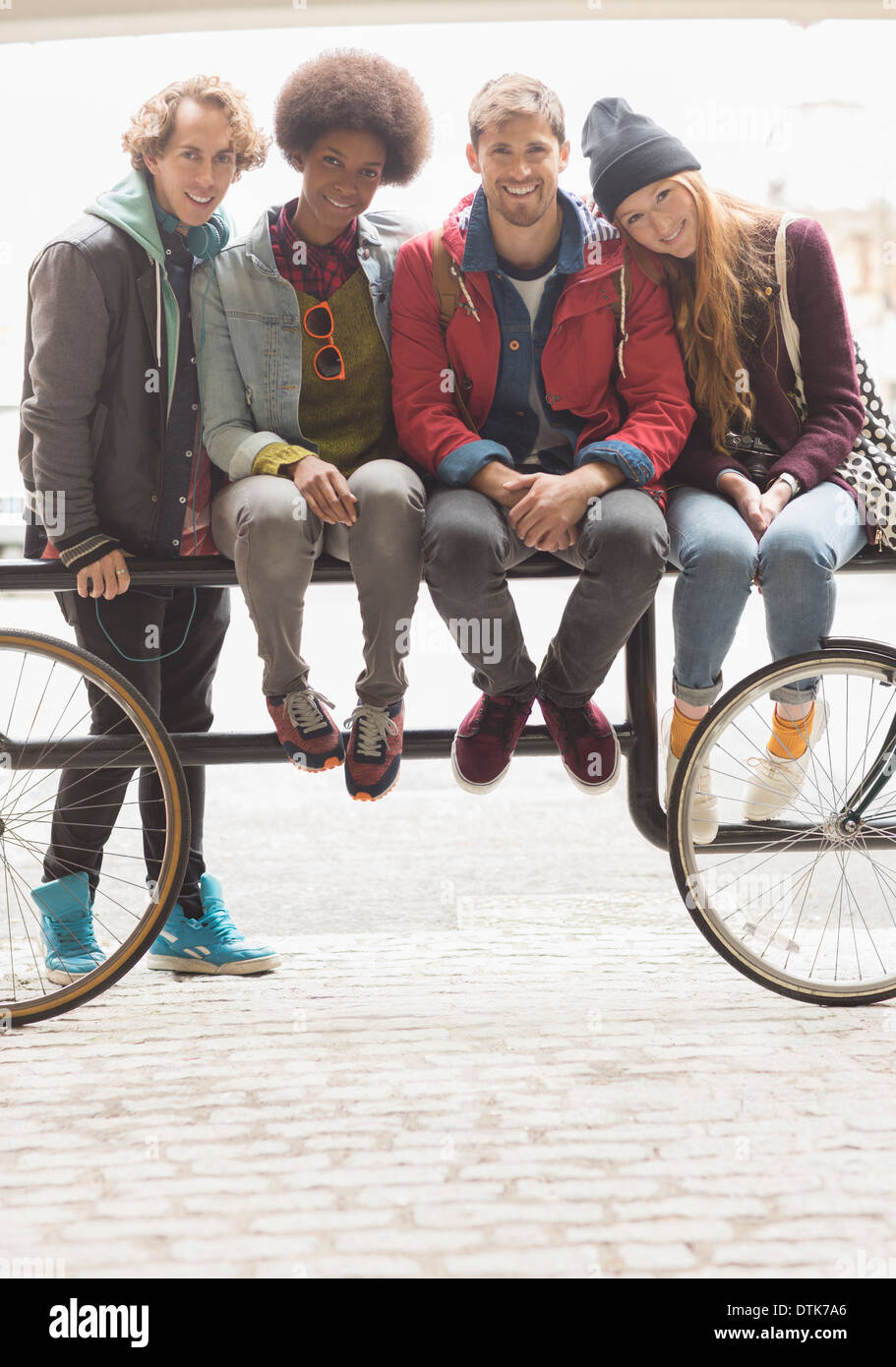 Friends smiling together on urban bike rack Stock Photo