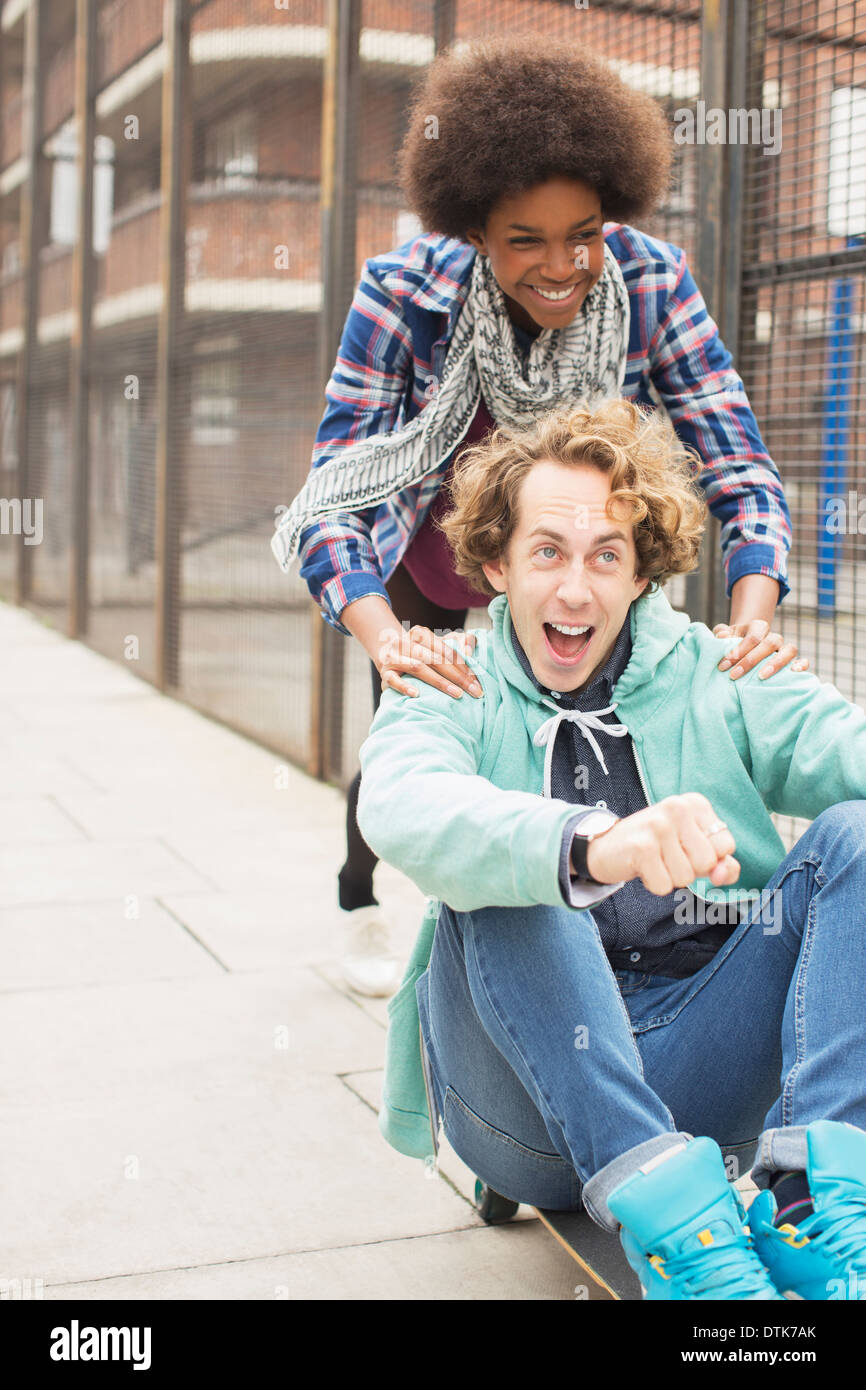 Couple playing on skateboard on city street Stock Photo