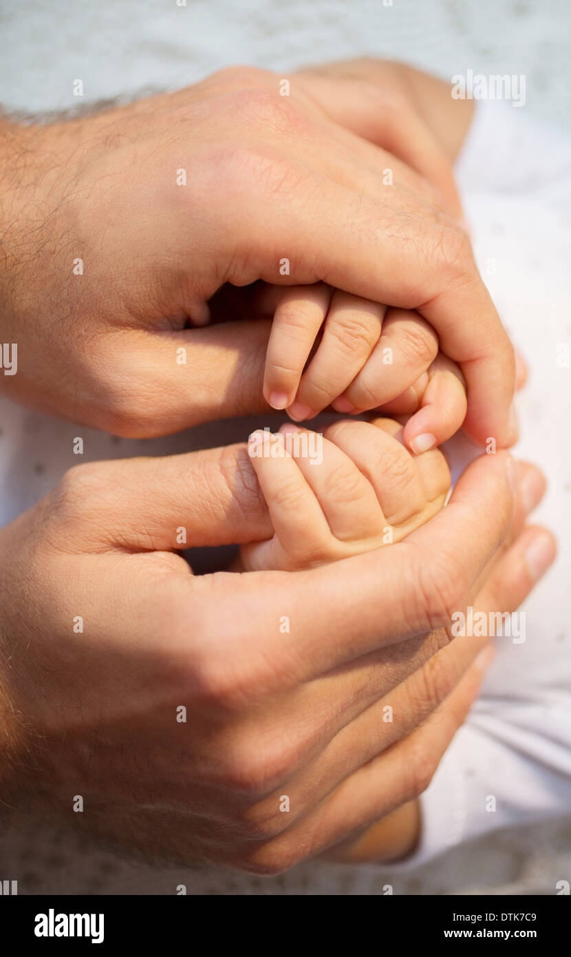 Father holding baby boy's hands - Stock Image