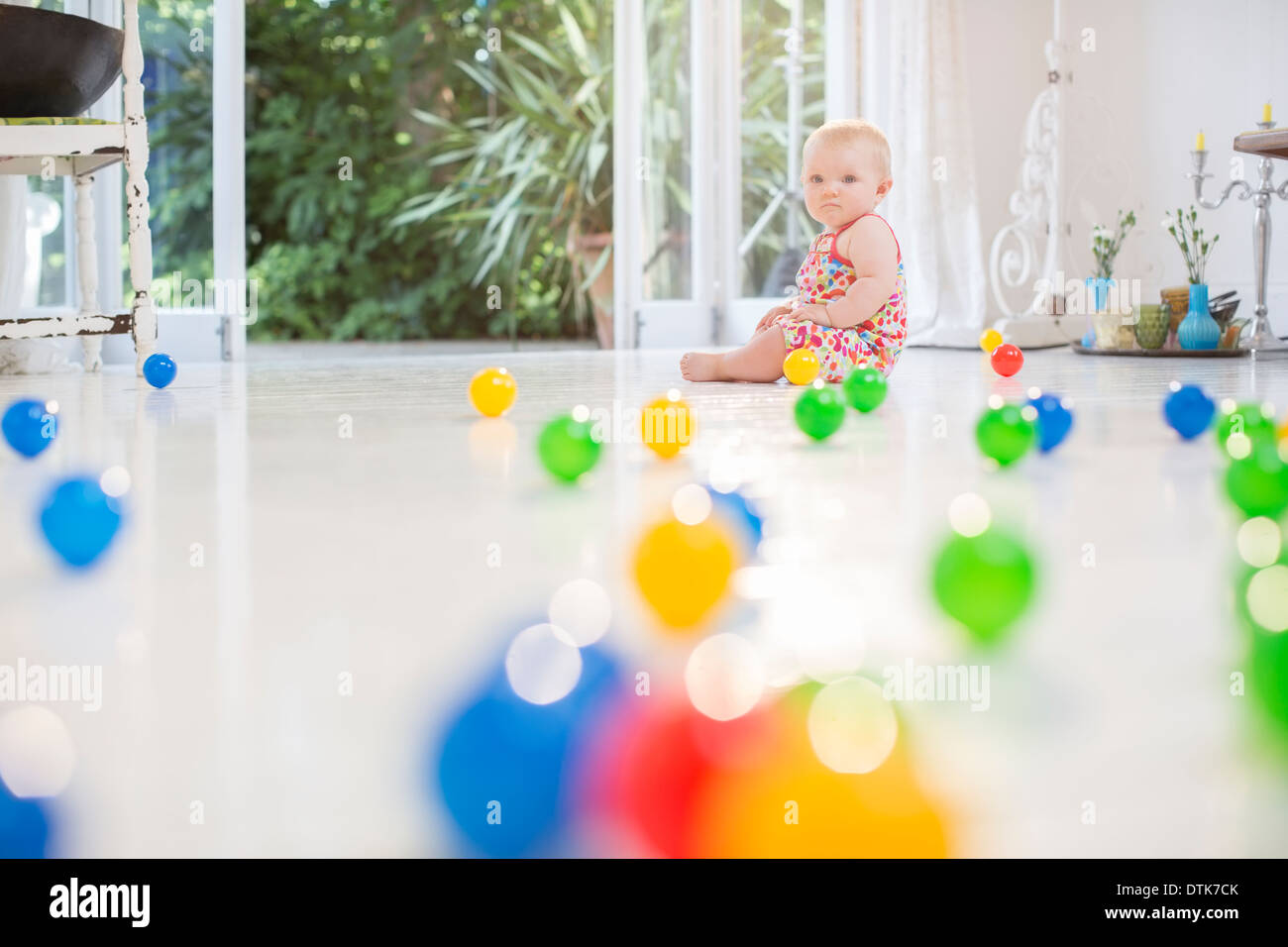 Baby girl with toys on kitchen floor - Stock Image