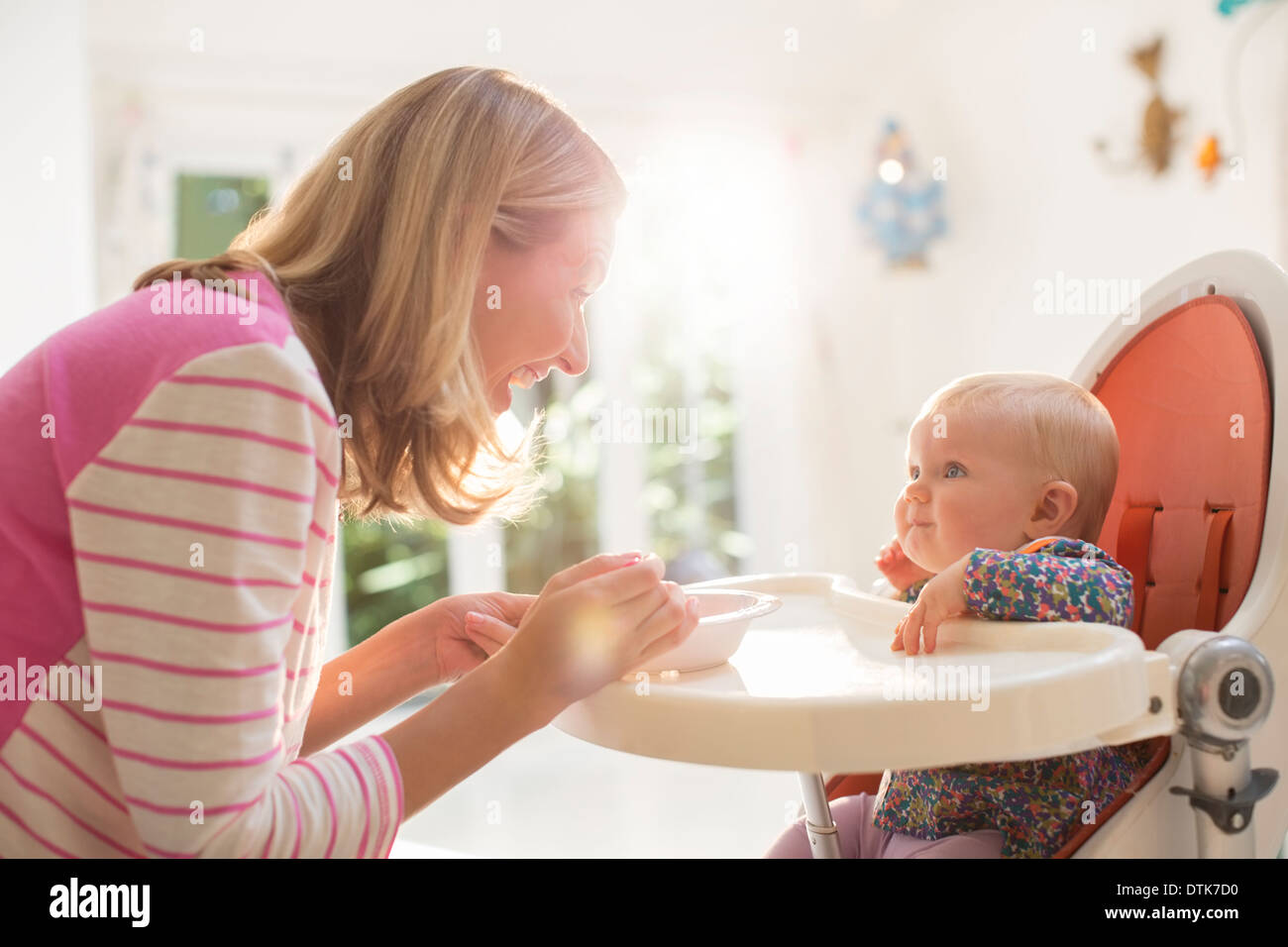 Mother feeding baby girl in high chair & Mother feeding baby girl in high chair Stock Photo: 66805788 - Alamy