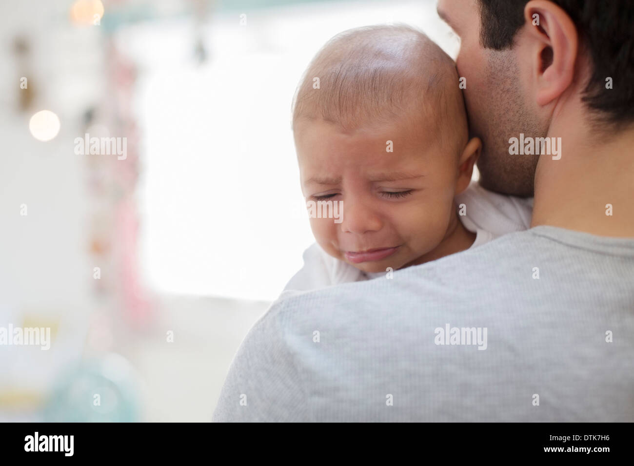 Father holding crying baby boy - Stock Image