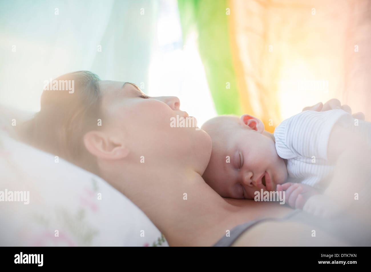 Mother and baby girl sleeping on bed Stock Photo