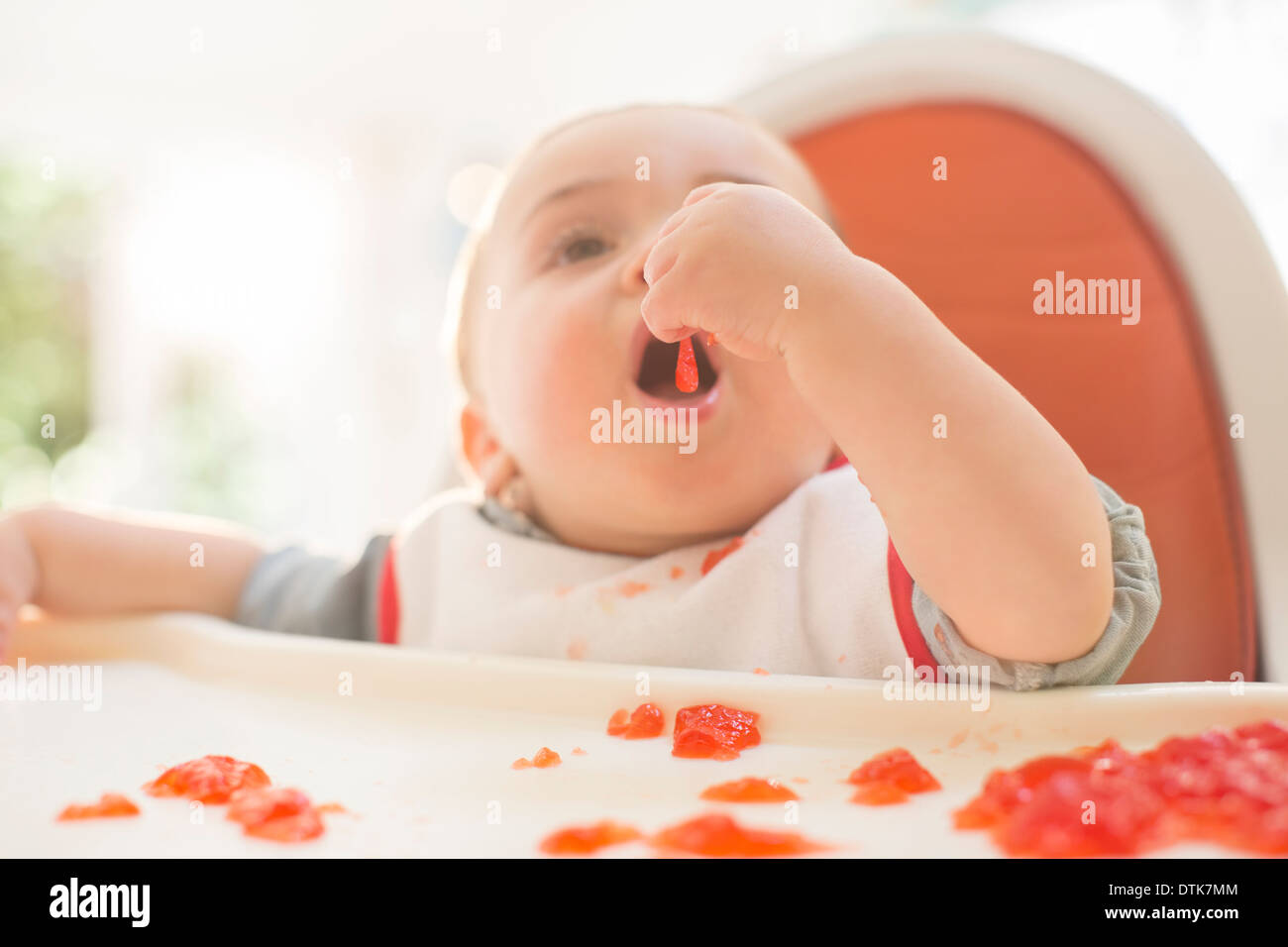 Baby boy eating in high chair - Stock Image