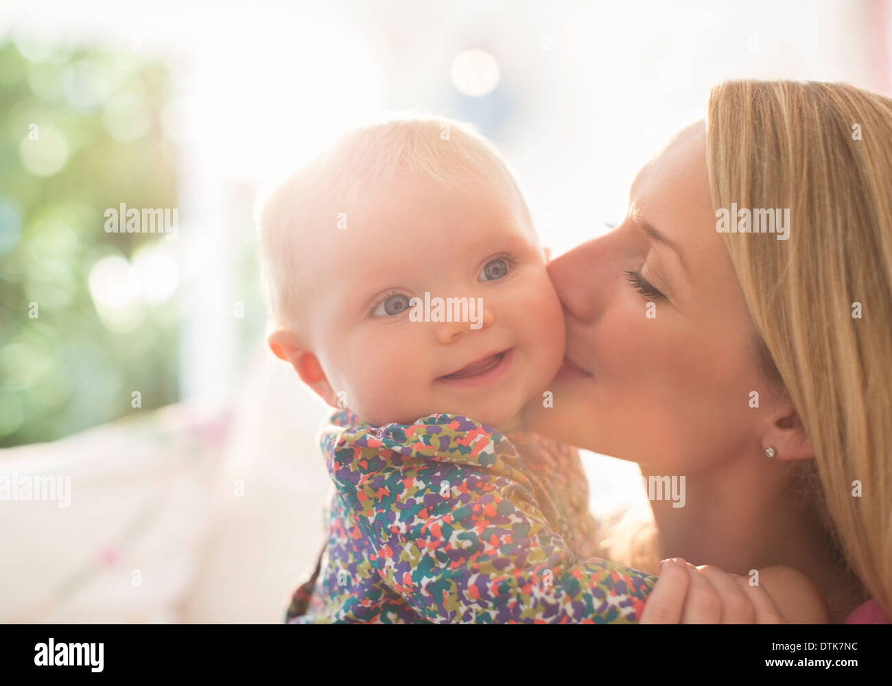 Mother kissing baby girl's cheek - Stock Image
