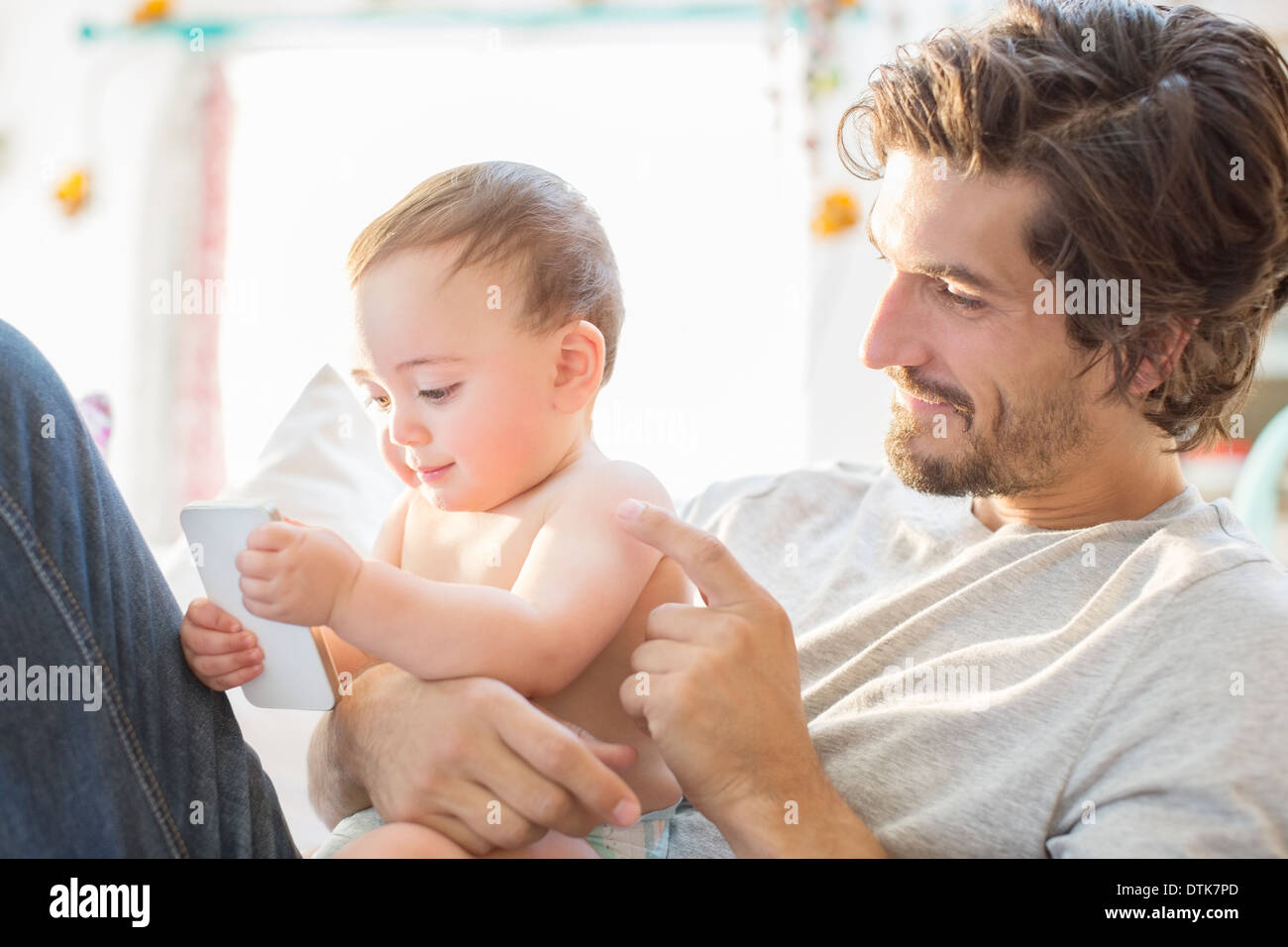 Father and baby boy playing with cell phone - Stock Image