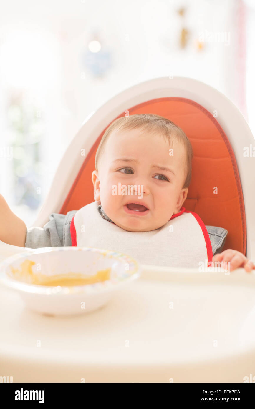 Baby boy crying in high chair - Stock Image