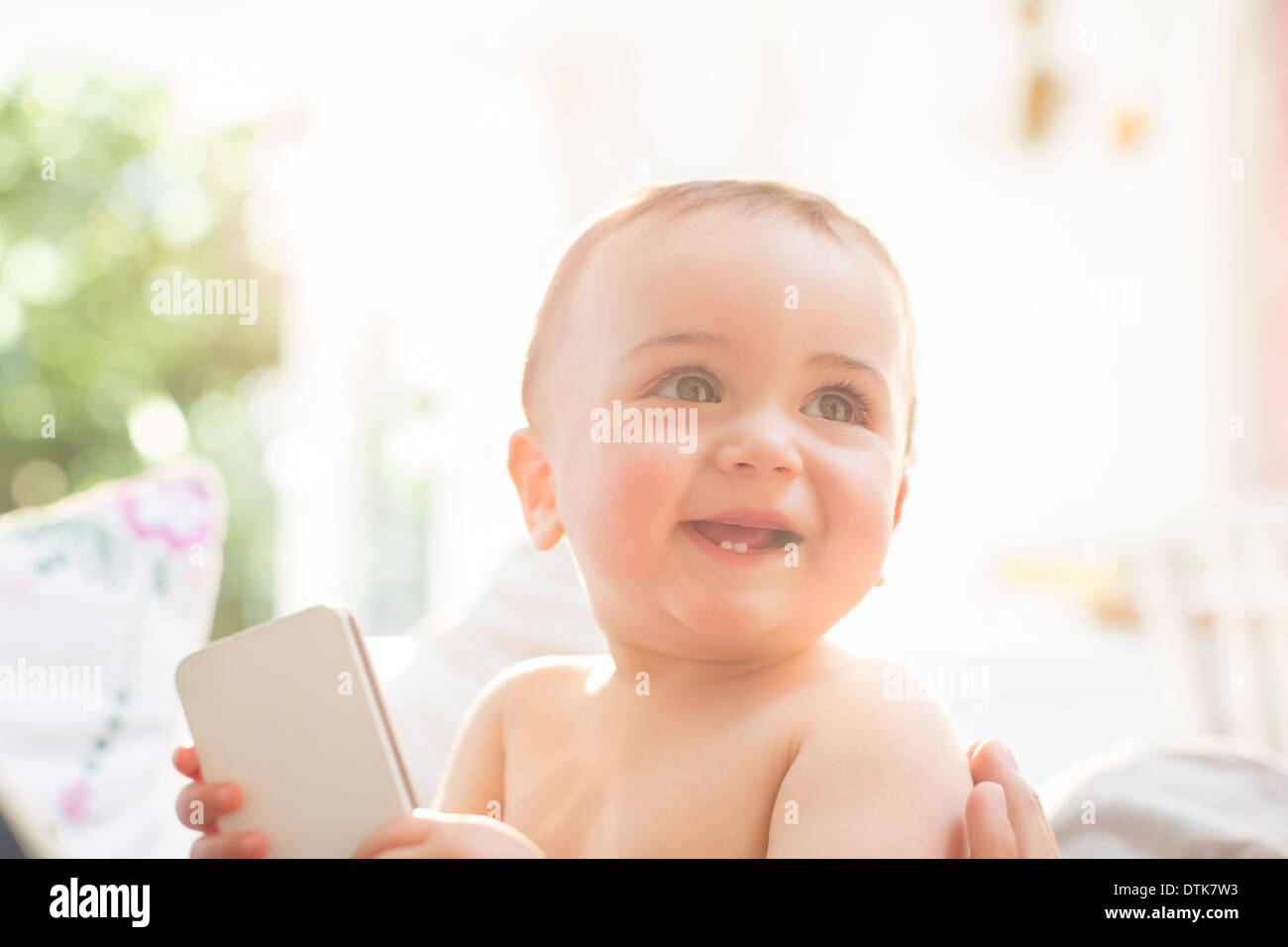 Baby boy playing with cell phone - Stock Image