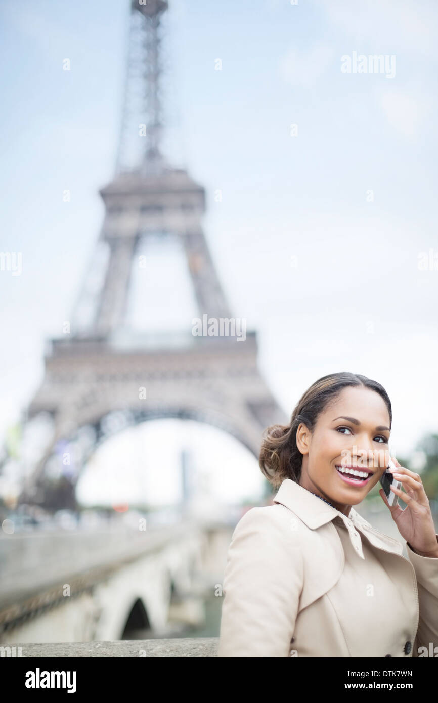 Woman talking on cell phone by Eiffel Tower, Paris, France Stock Photo
