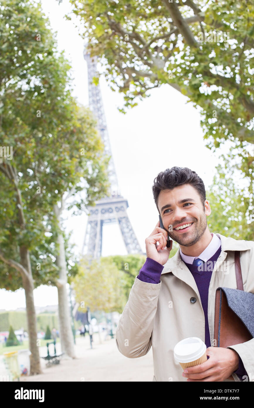 Businessman talking on cell phone near Eiffel Tower, Paris, France - Stock Image