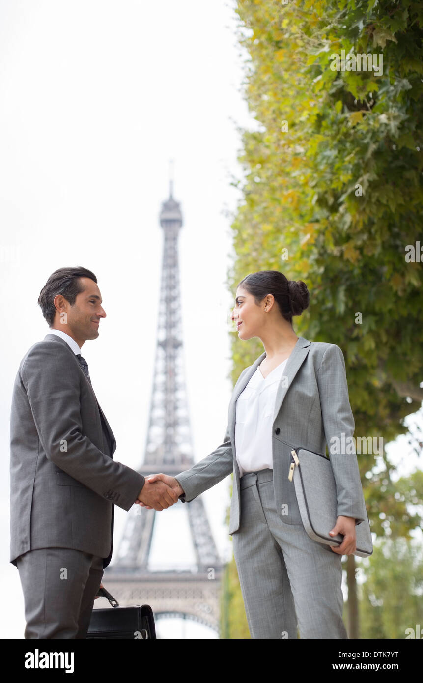 Business people shaking hands near Eiffel Tower, Paris, France - Stock Image