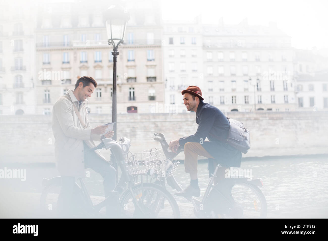 Businessmen talking on bicycles along Seine River, Paris, France - Stock Image
