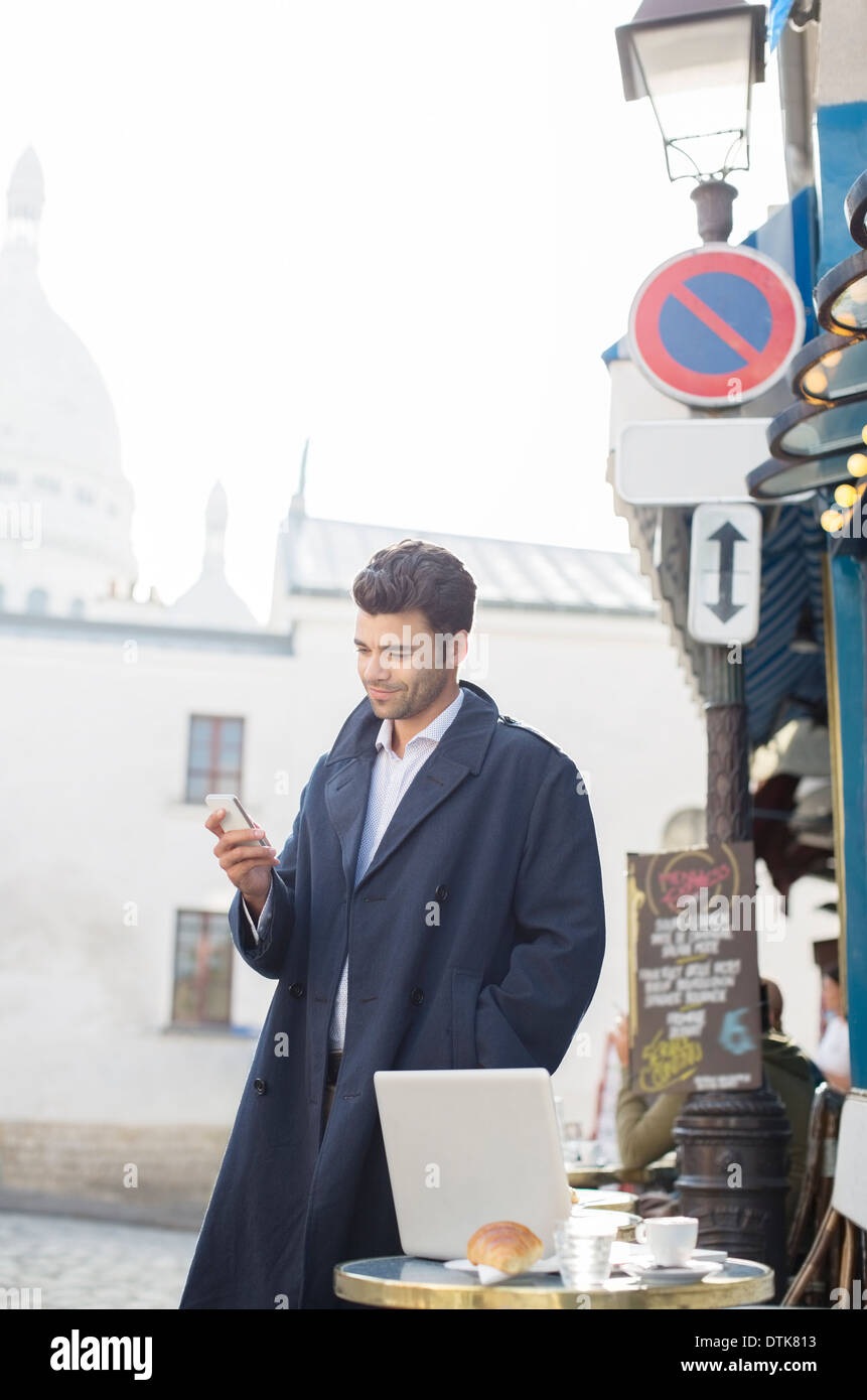 Businessman using cell phone at sidewalk cafe - Stock Image