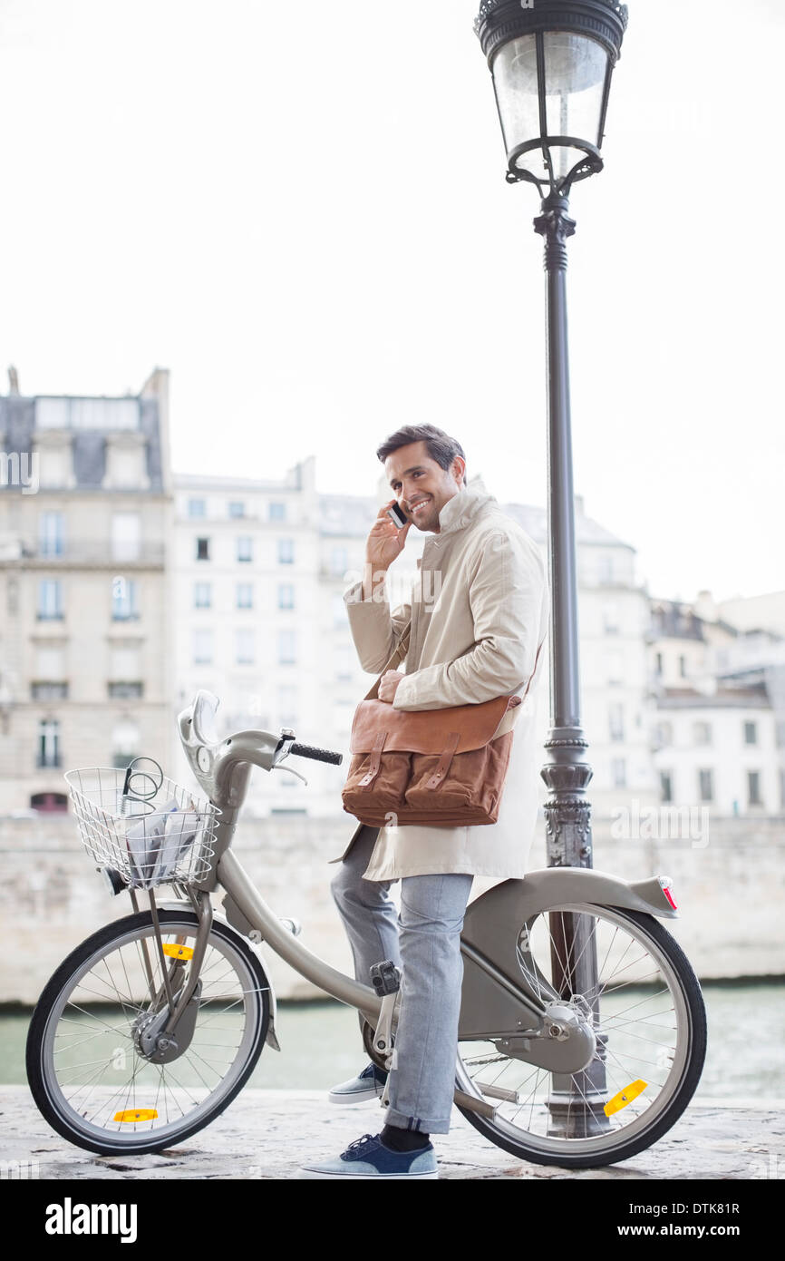 Businessman talking on cell phone on bicycle along Seine River, Paris, France - Stock Image
