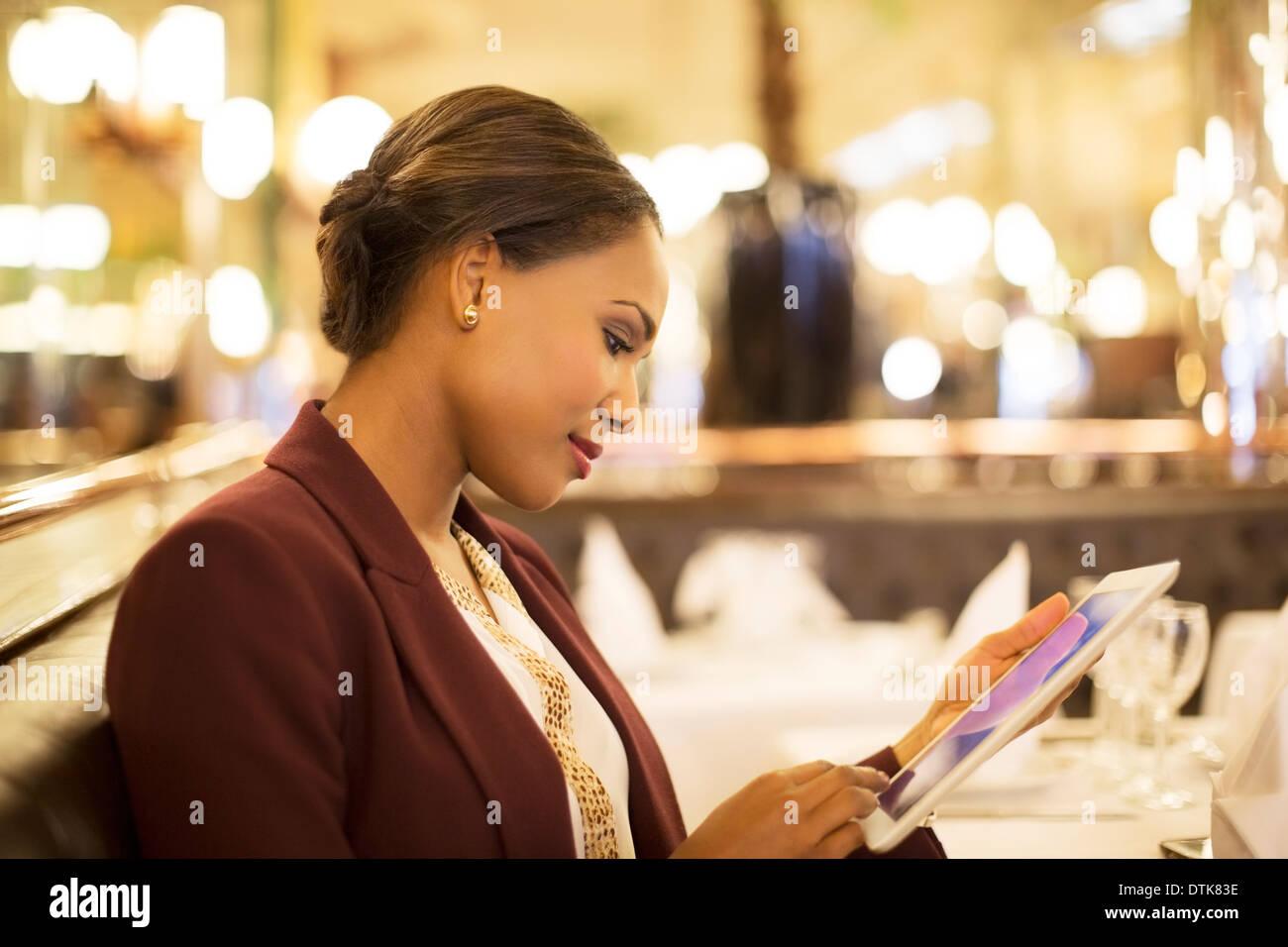Businesswoman using digital tablet in restaurant - Stock Image