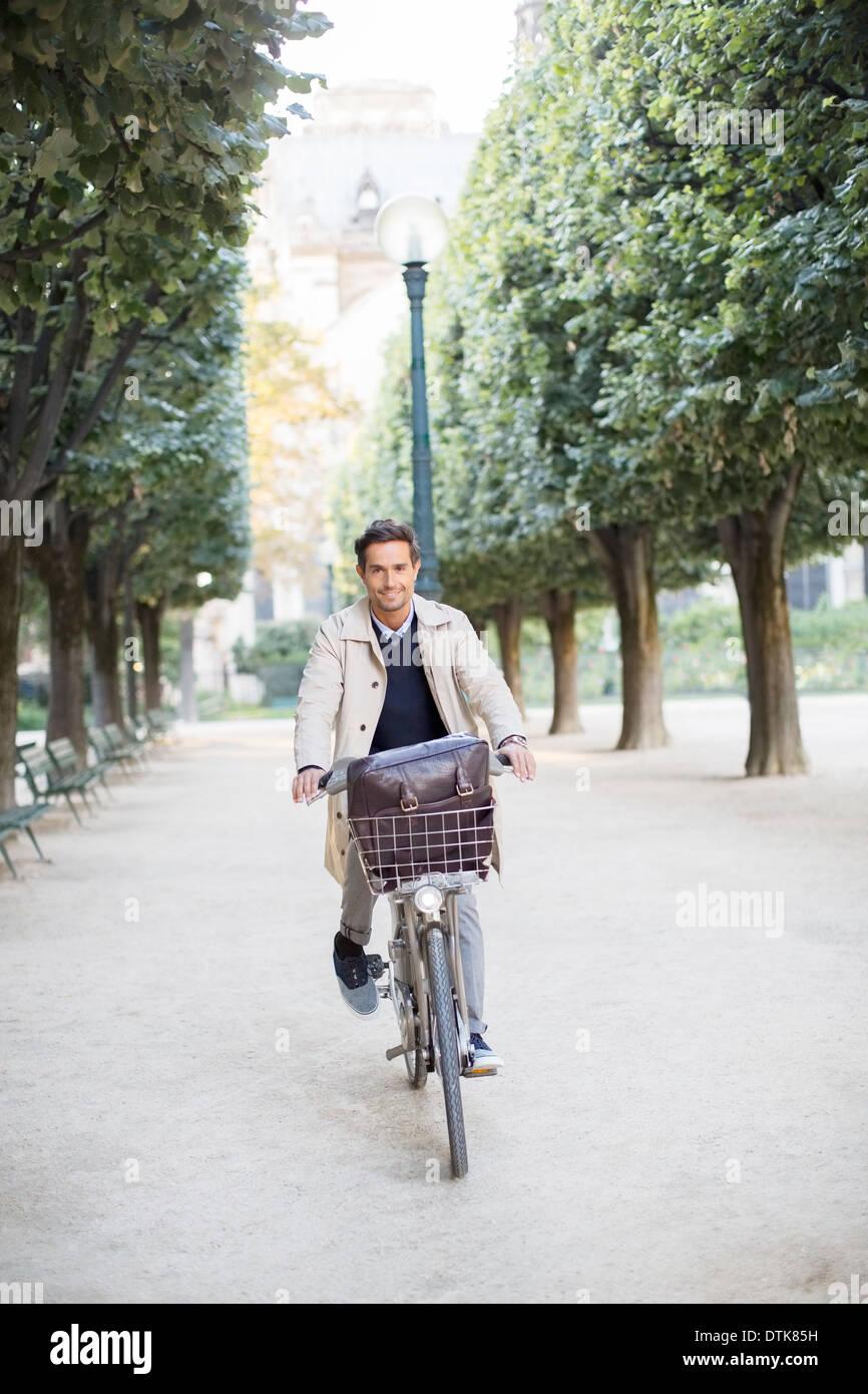 Businessman riding bicycle in park, Paris, France Stock Photo