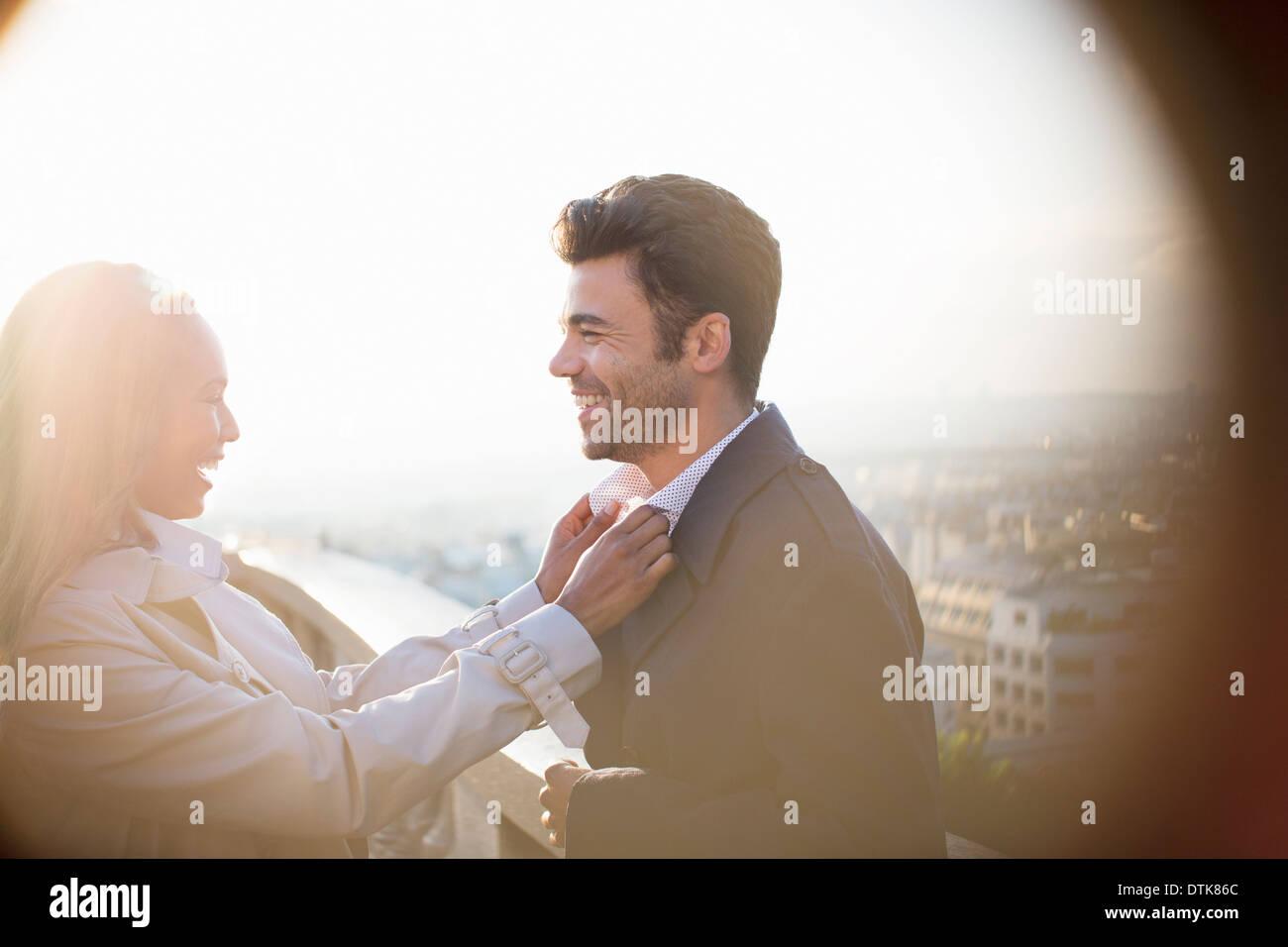 Woman holding boyfriend's collar on urban balcony - Stock Image