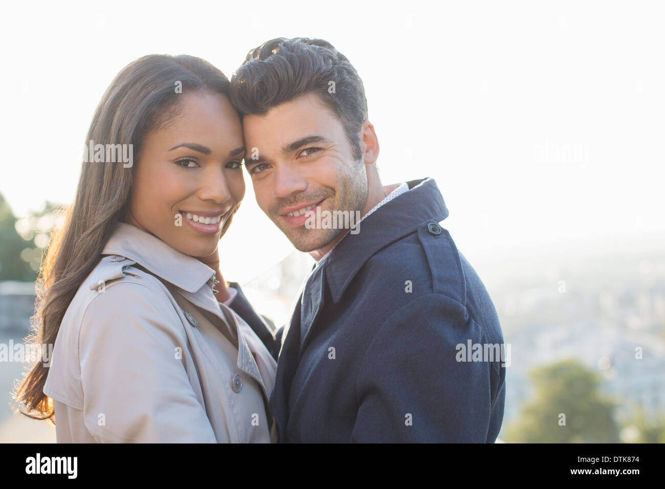 Couple in trench coats hugging - Stock Image