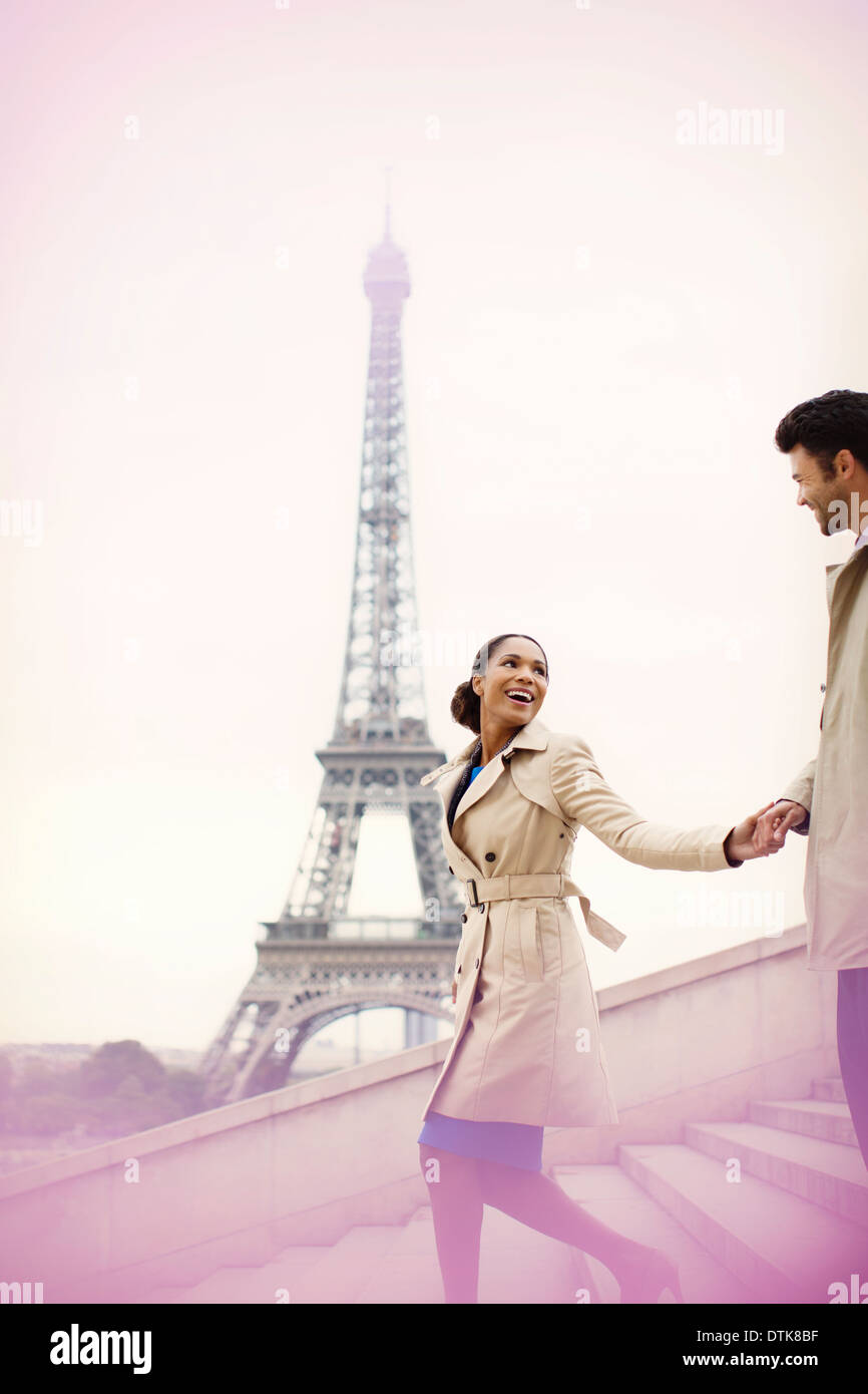 Couple descending stairs by Eiffel Tower, Paris, France - Stock Image