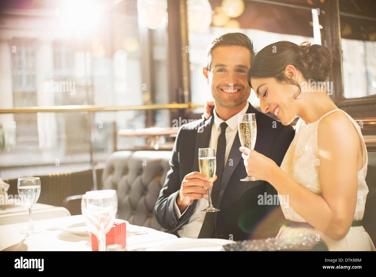 Well-dressed couple drinking champagne in restaurant - Stock Image