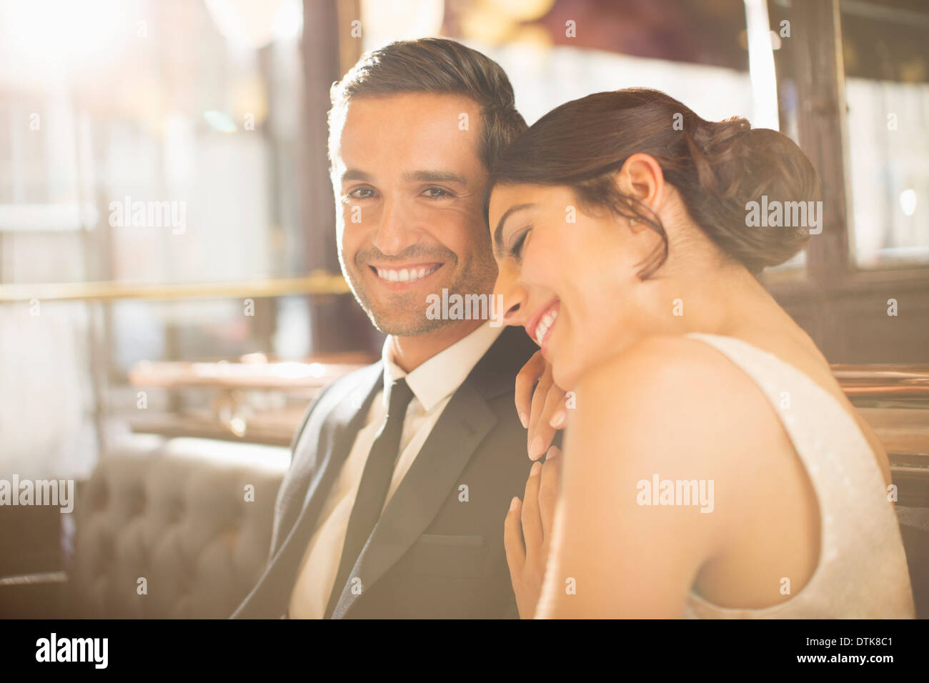 Well-dressed couple hugging in restaurant - Stock Image