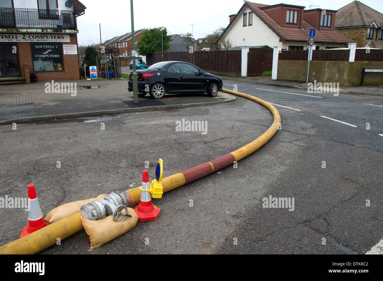 Flooded residential area and park in Staines. Water being pumped with yellow hosepipe. - Stock Image