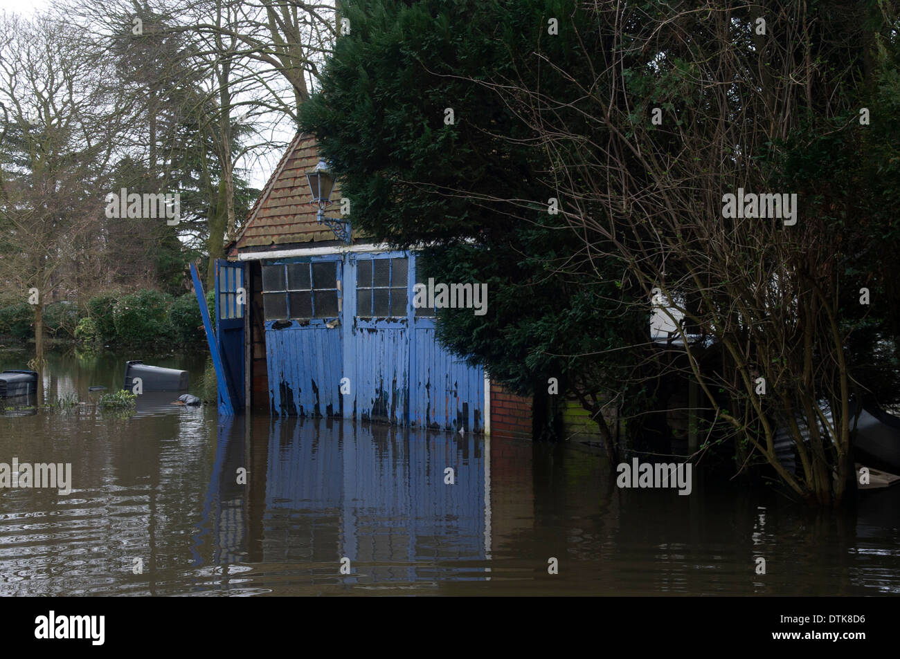 Flooded residential area and park in Staines. Set of old blue wooden garage doors and side of house. - Stock Image