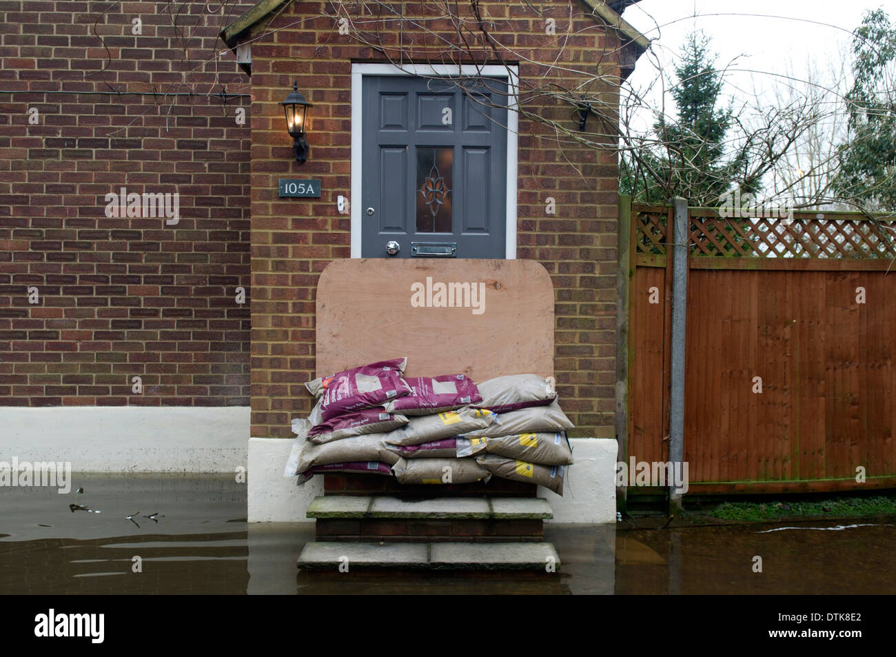 Flooded residential area and park in Staines. Driveway totally flooded with sandbags and wooden board covering front door and steps for protection. Driveway has twin white garages. - Stock Image