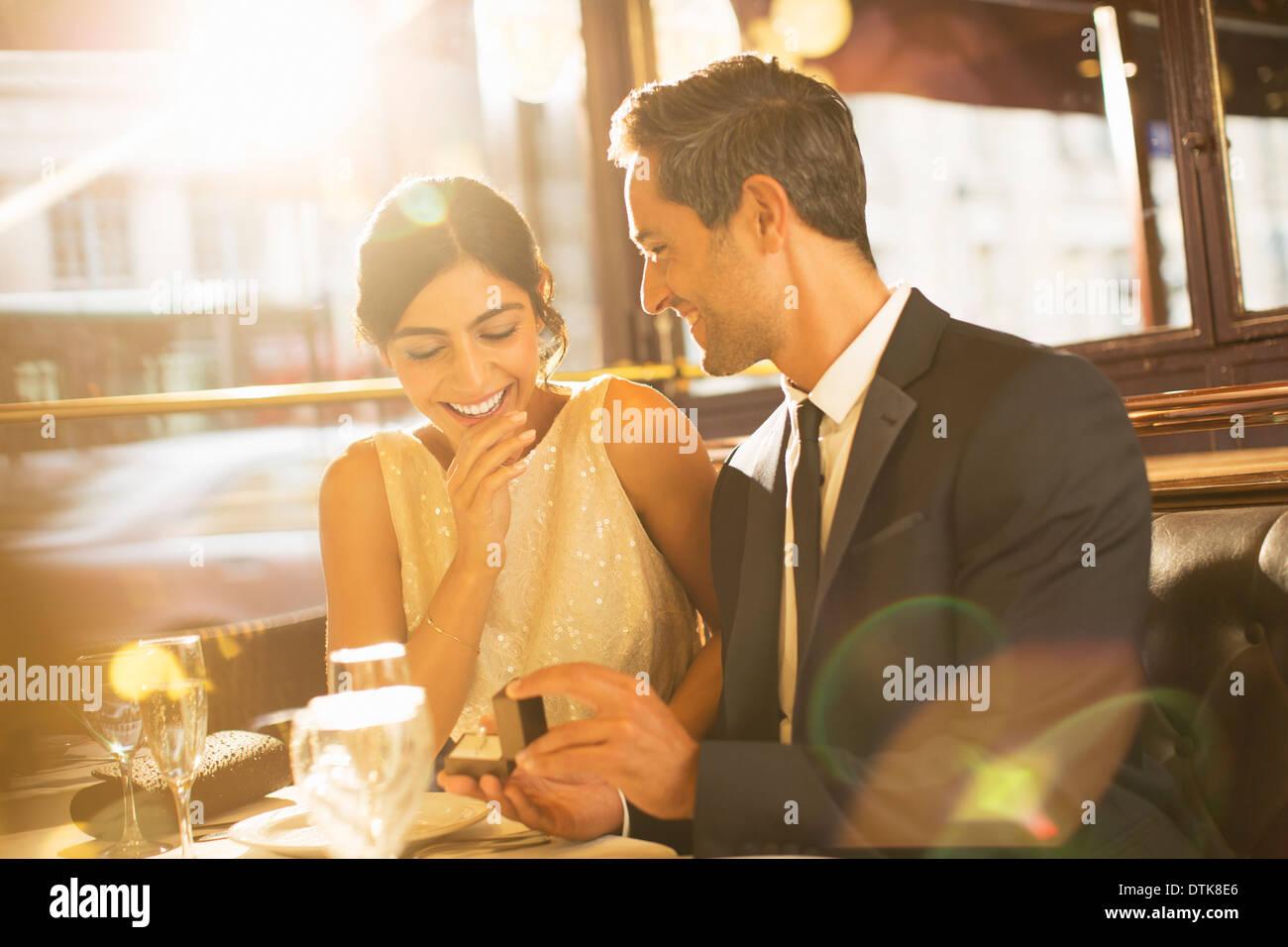Man proposing to girlfriend in restaurant - Stock Image