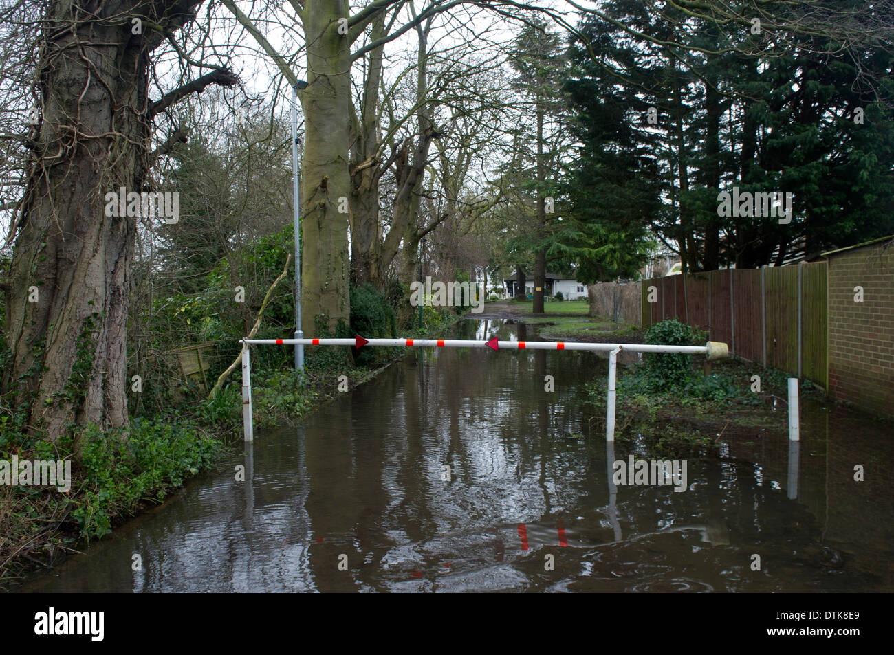 Flooded residential area and park in Staines. Driveway totally flooded with closed barrier to restrict access. - Stock Image