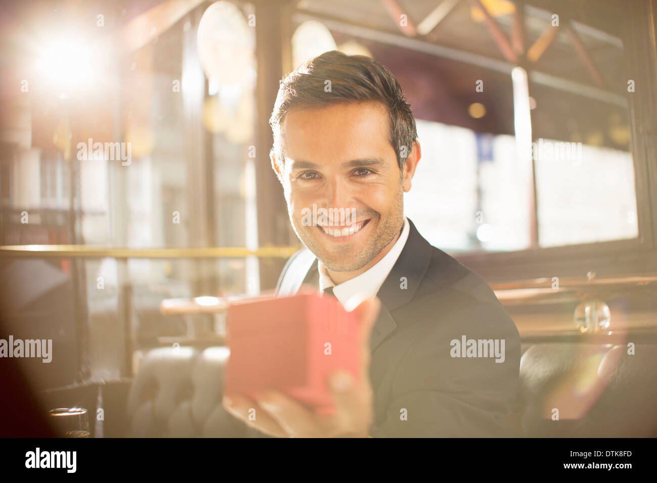 Well-dressed man holding jewelry box in restaurant - Stock Image