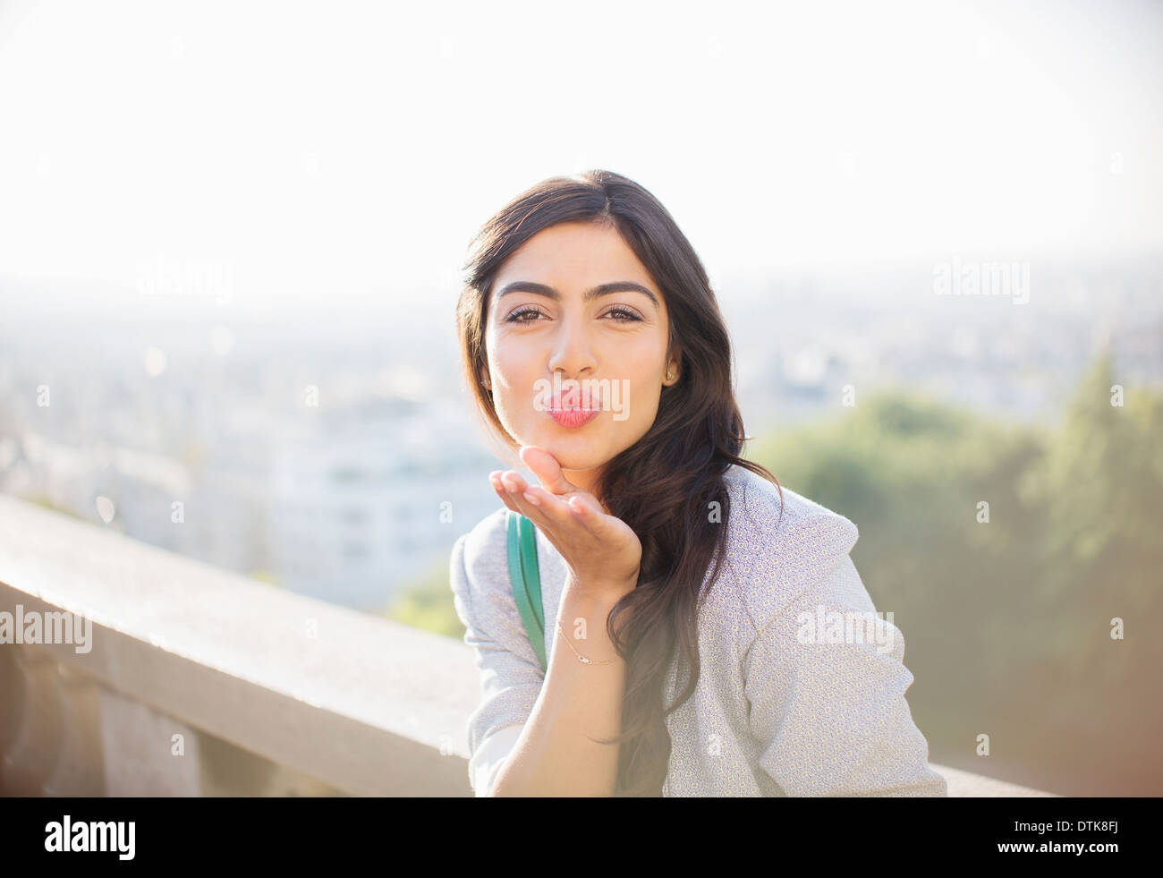 Woman blowing a kiss outdoors - Stock Image