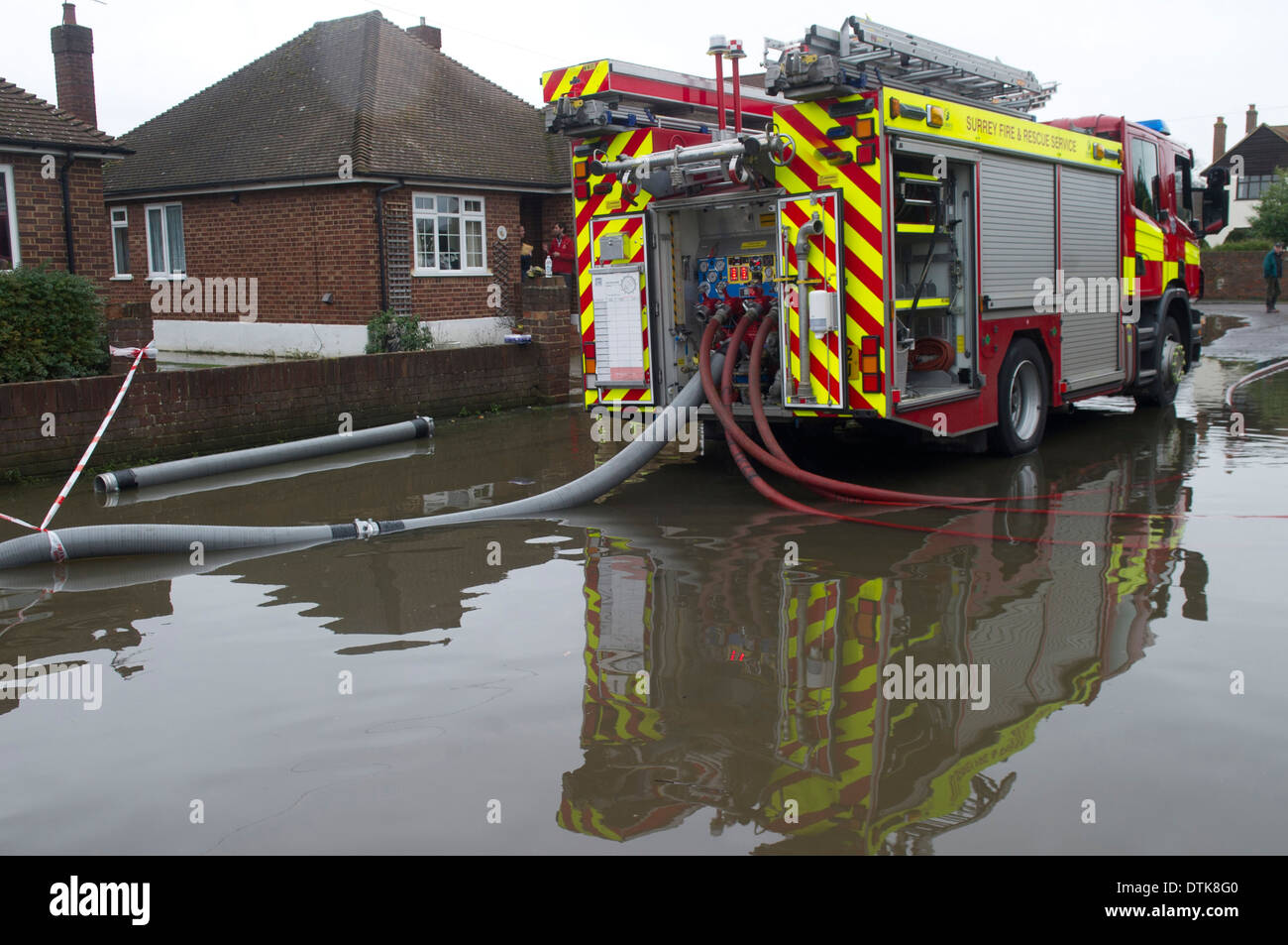 Flooded residential area and park in Staines. Driveway and streets flooded. Fire brigade pumping water from front gardens. - Stock Image
