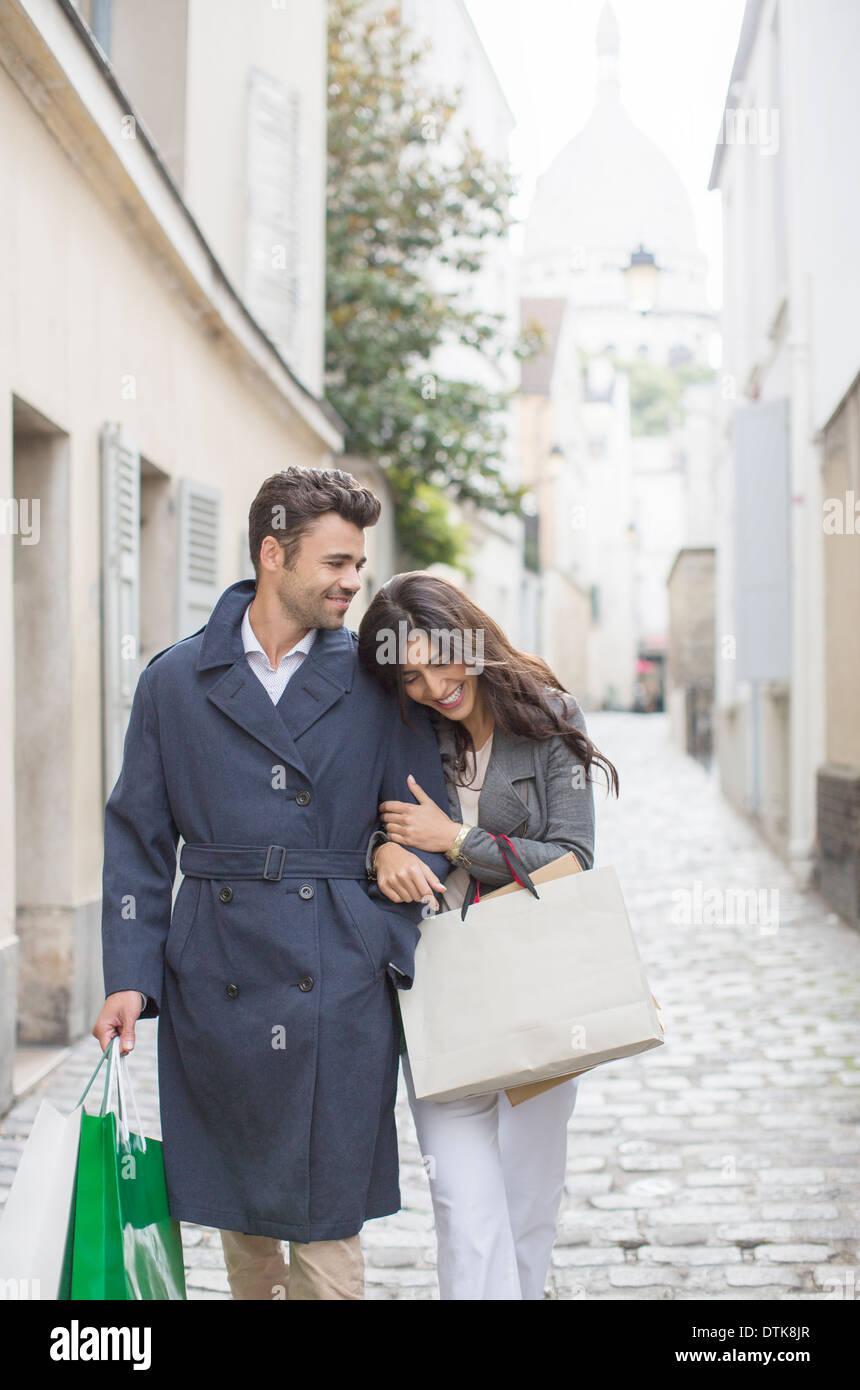 Couple carrying shopping bags on cobblestone street near Sacre Coeur Basilica, Paris, France - Stock Image