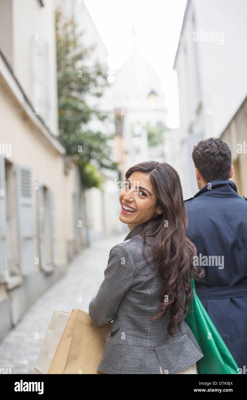 Couple carrying shopping bags in street near Sacre Coeur Basilica, Paris, France Stock Photo