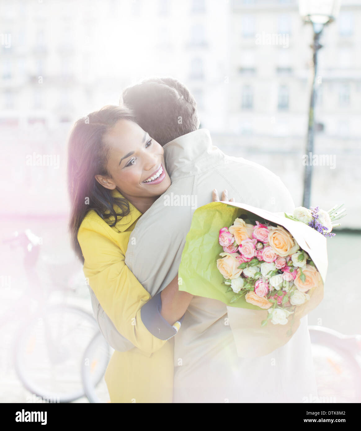 Couple with bouquet of flowers hugging along Seine River, Paris, France - Stock Image