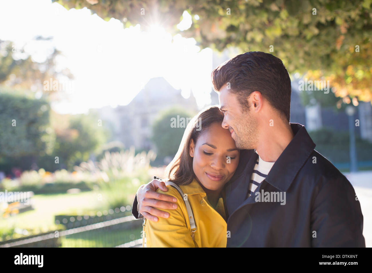 Couple hugging in urban park - Stock Image