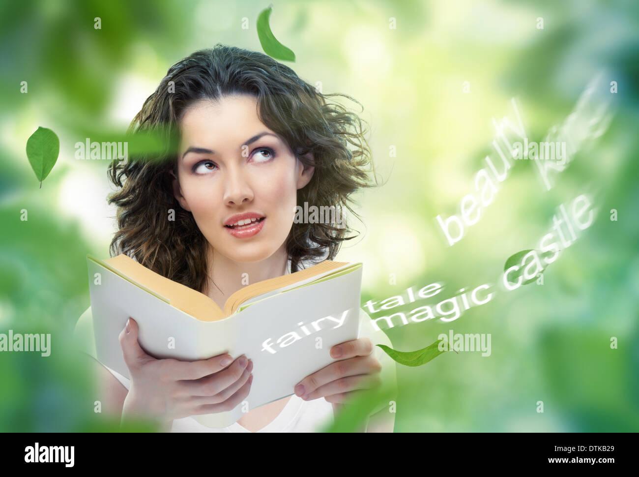 young beautiful girl reading a magic book - Stock Image