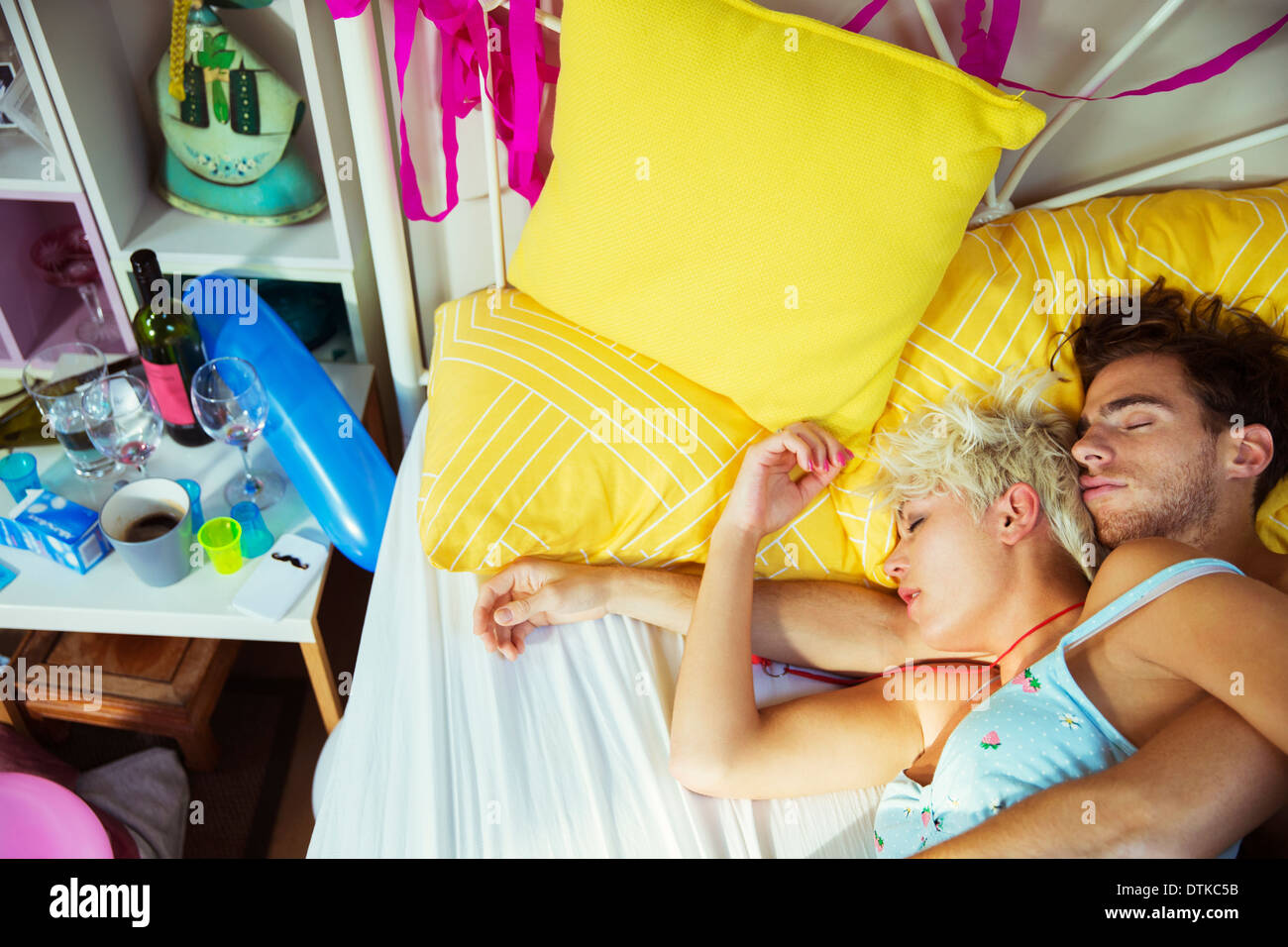 Couple sleeping in bed after party - Stock Image