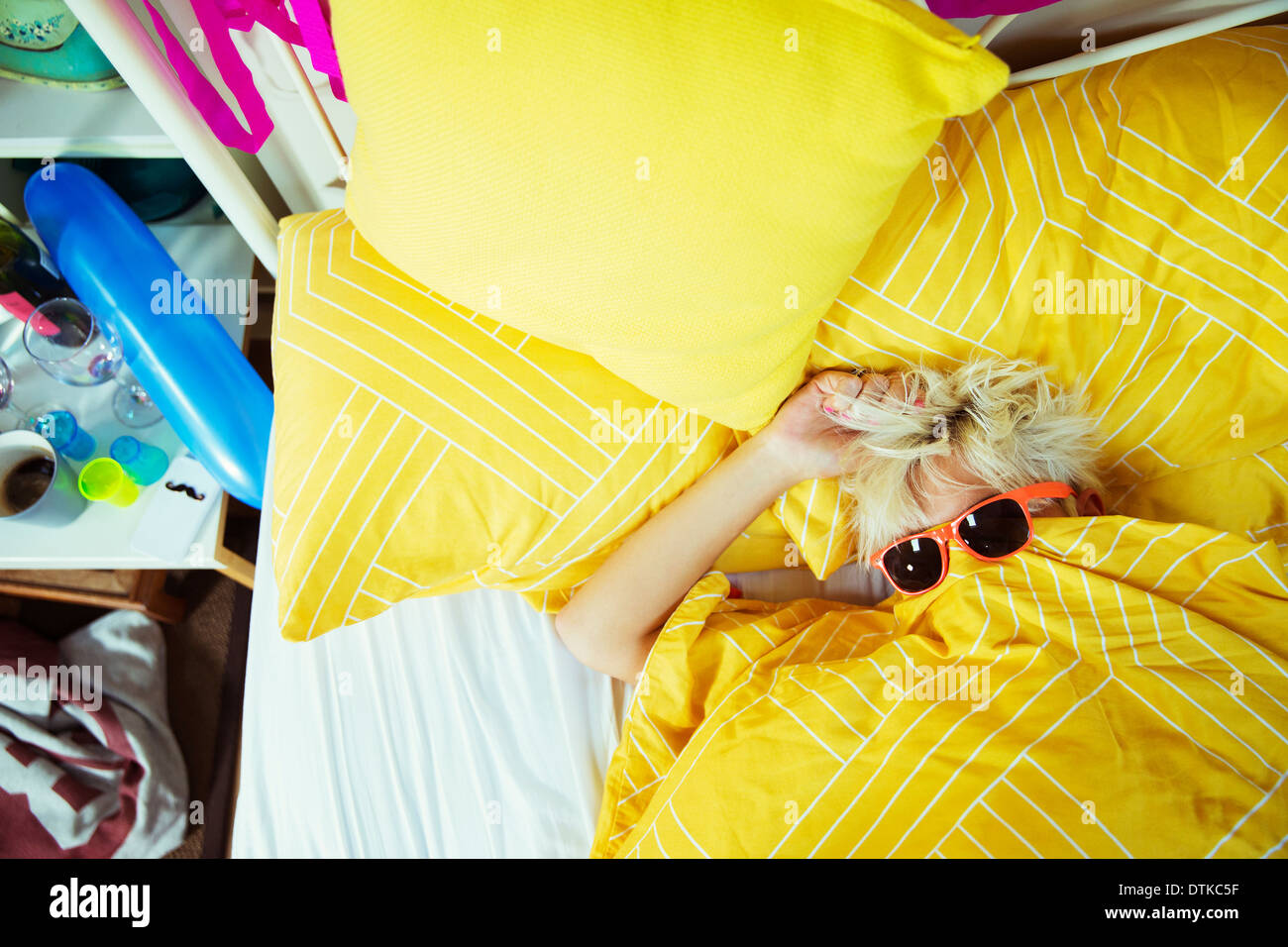 Woman wearing sunglasses in bed after party - Stock Image