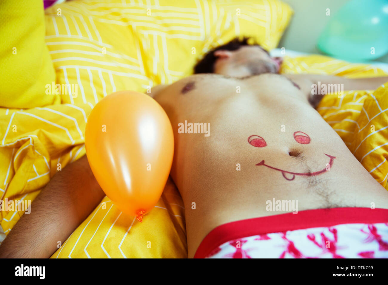 Man with smiley face drawing on belly sleeping after party - Stock Image