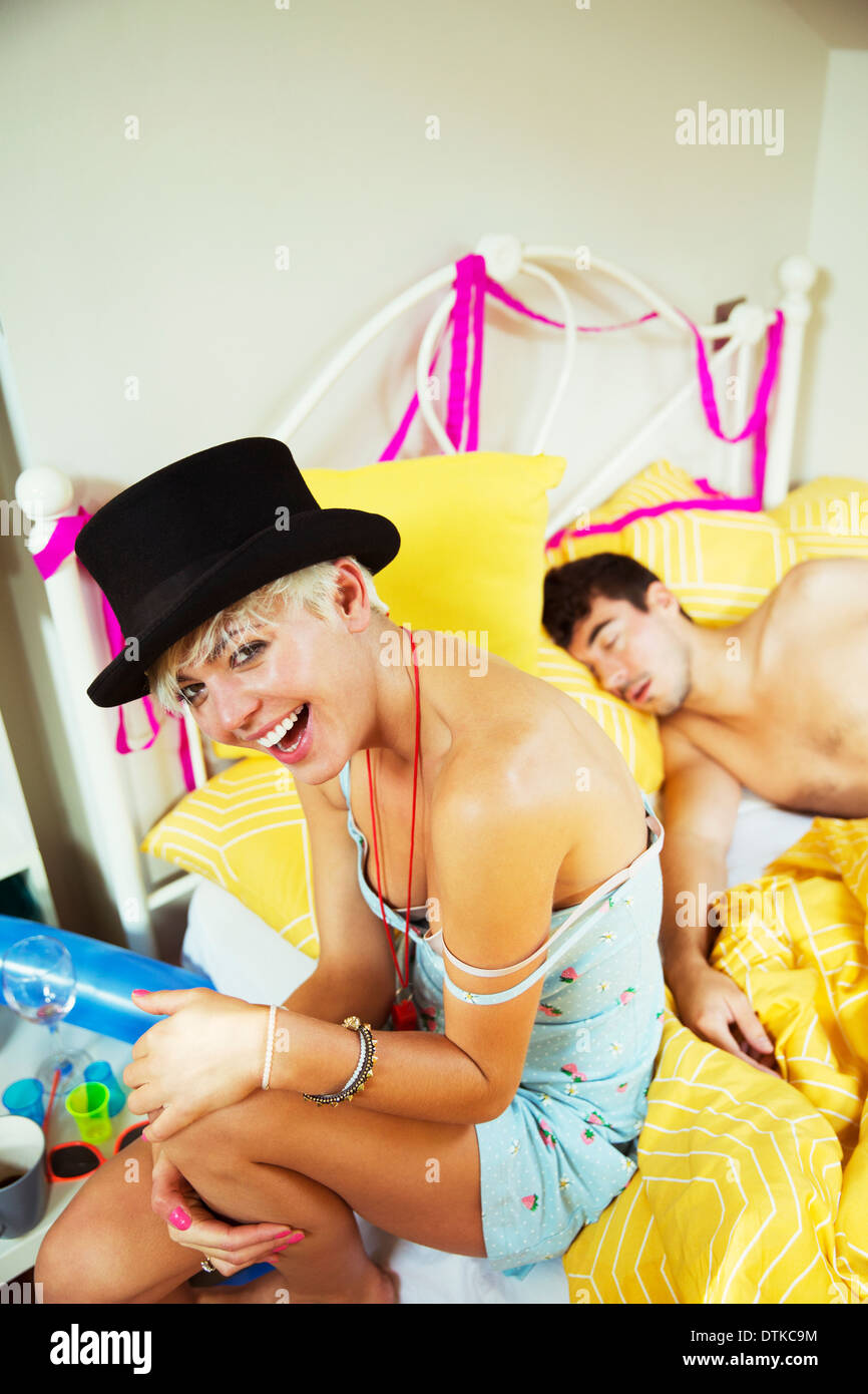 Laughing woman sitting on bed the morning after a party - Stock Image