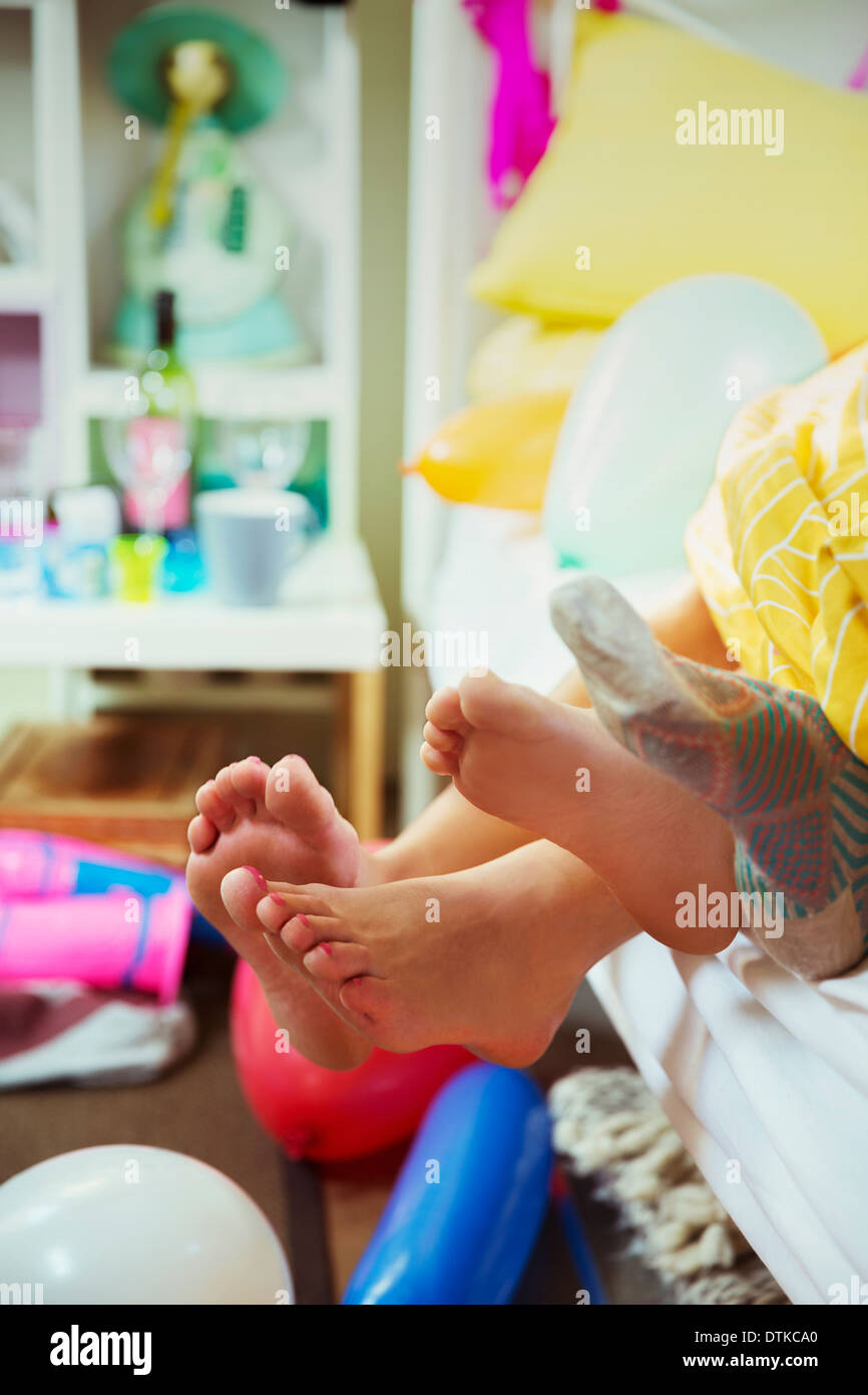 Couple's feet sticking out from bed covers - Stock Image